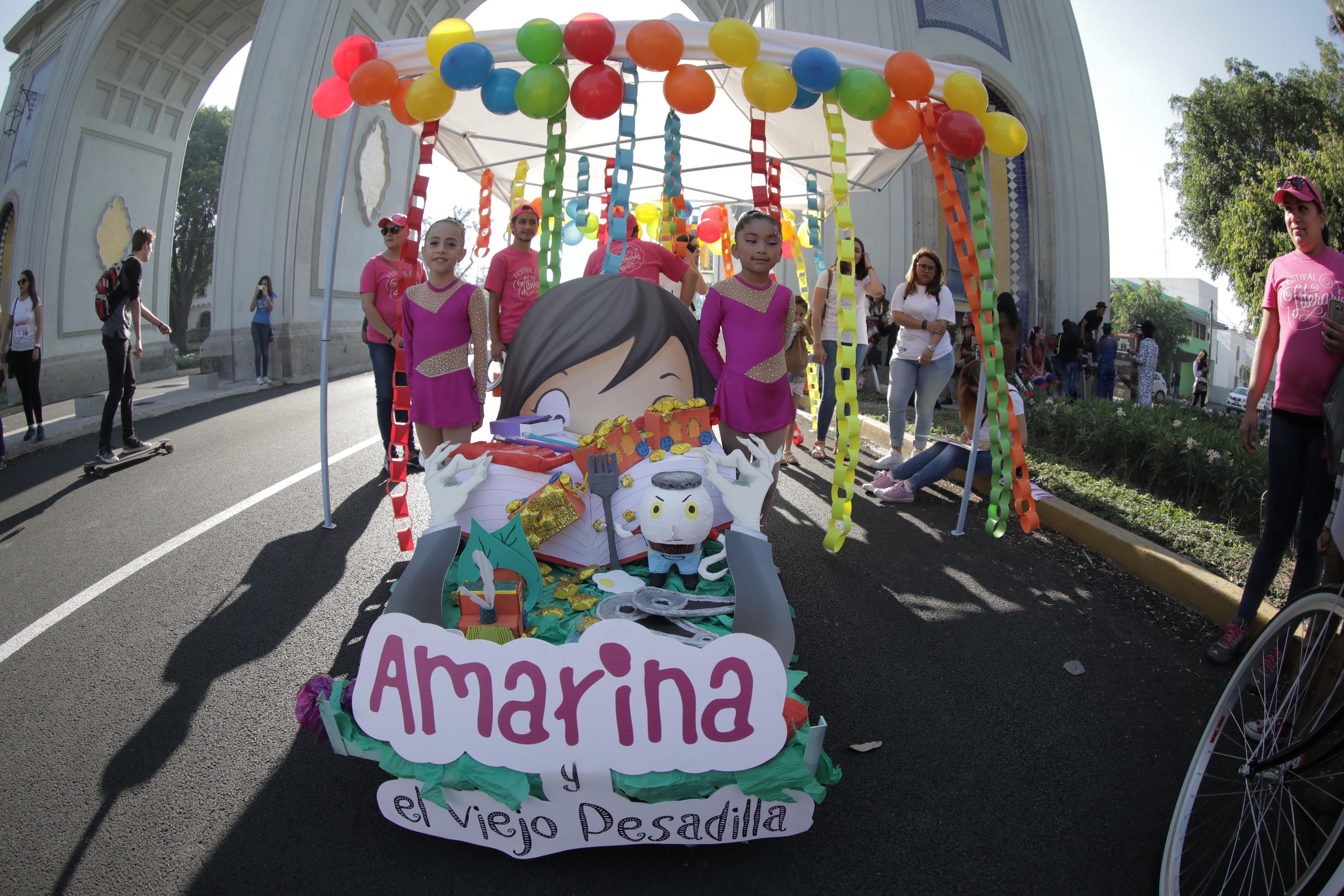 """Carro alegórico representando la obra """"Amarina y el viejo pesadilla"""", acompañado de niñas de gimnasia rítmica."""