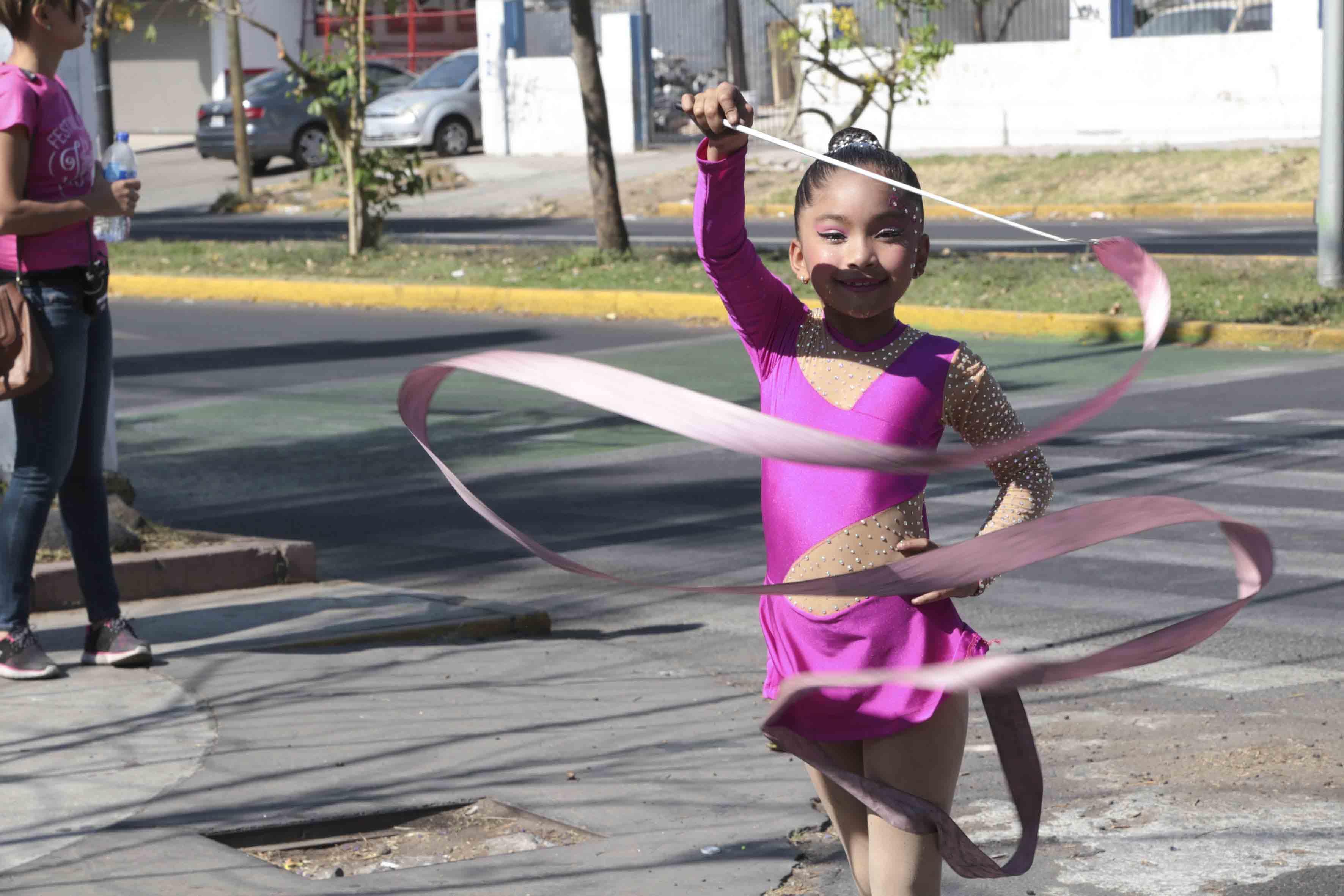 Niña practicando la gimnasia rítmica, durante el desfile del Primer Festival Literario.