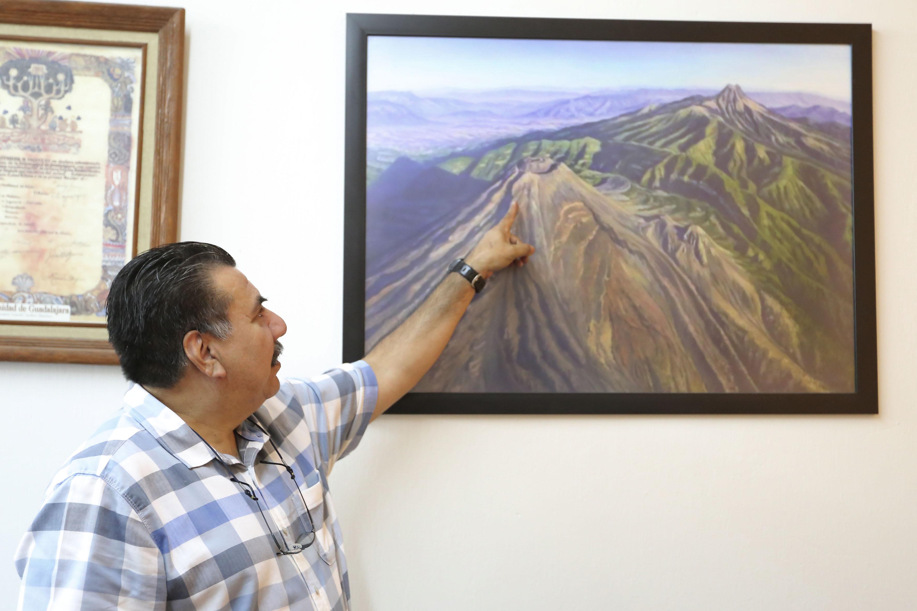 Doctor Carlos Suárez Plascencia, jefe del Departamento de Geografía y Ordenación Territorial, del Centro Universitario de Ciencias Sociales y Humanidades, señalando con su dedo índice a los volcanes de colima, plasmados en la pintura de un cuadro.