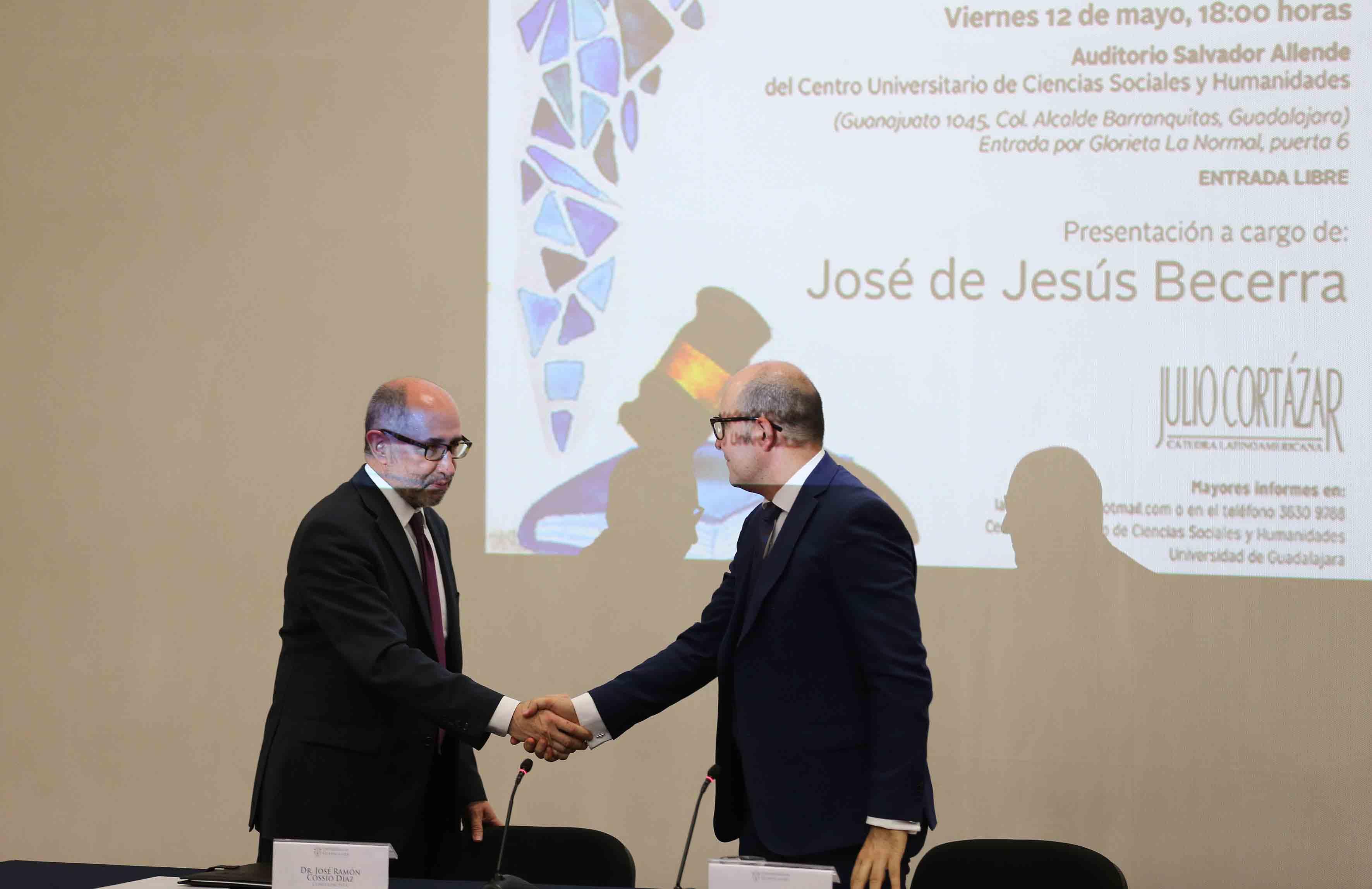 Doctores José Ramón Cossío Díaz y José de Jesús Becerra Ramírez, compartiendo saludo de mano.