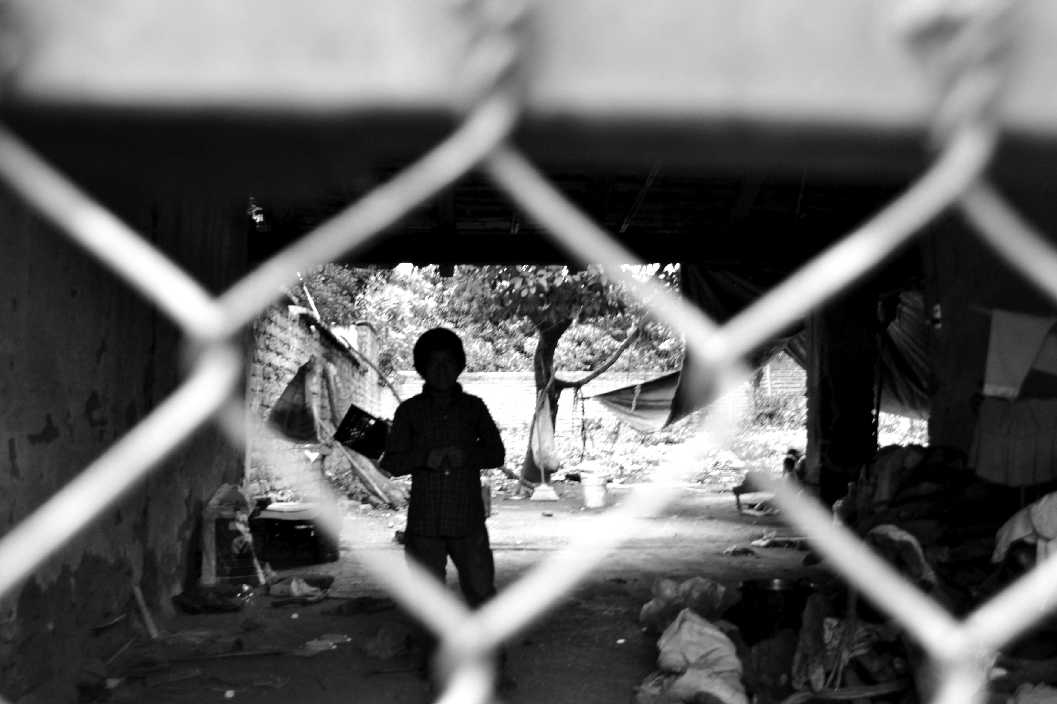 Silueta de un niño, detrás de una reja de alambre y en un ambiente desordenado.