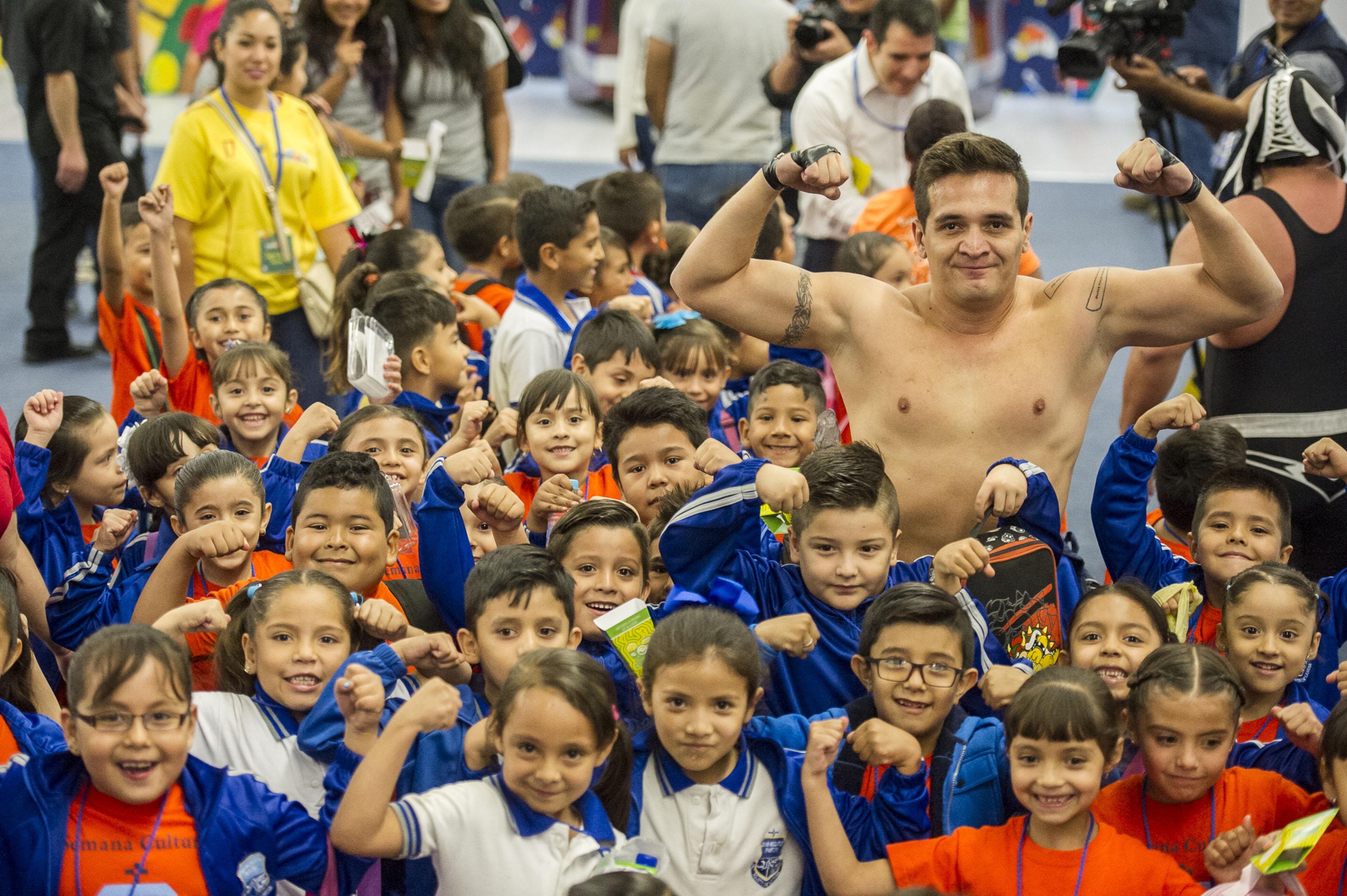 Niños escolares asistentes a Papirolas 2017, alzando sus brazos a lo alto en señal de fuerza, al conjunto e imitación del deportista luchador.