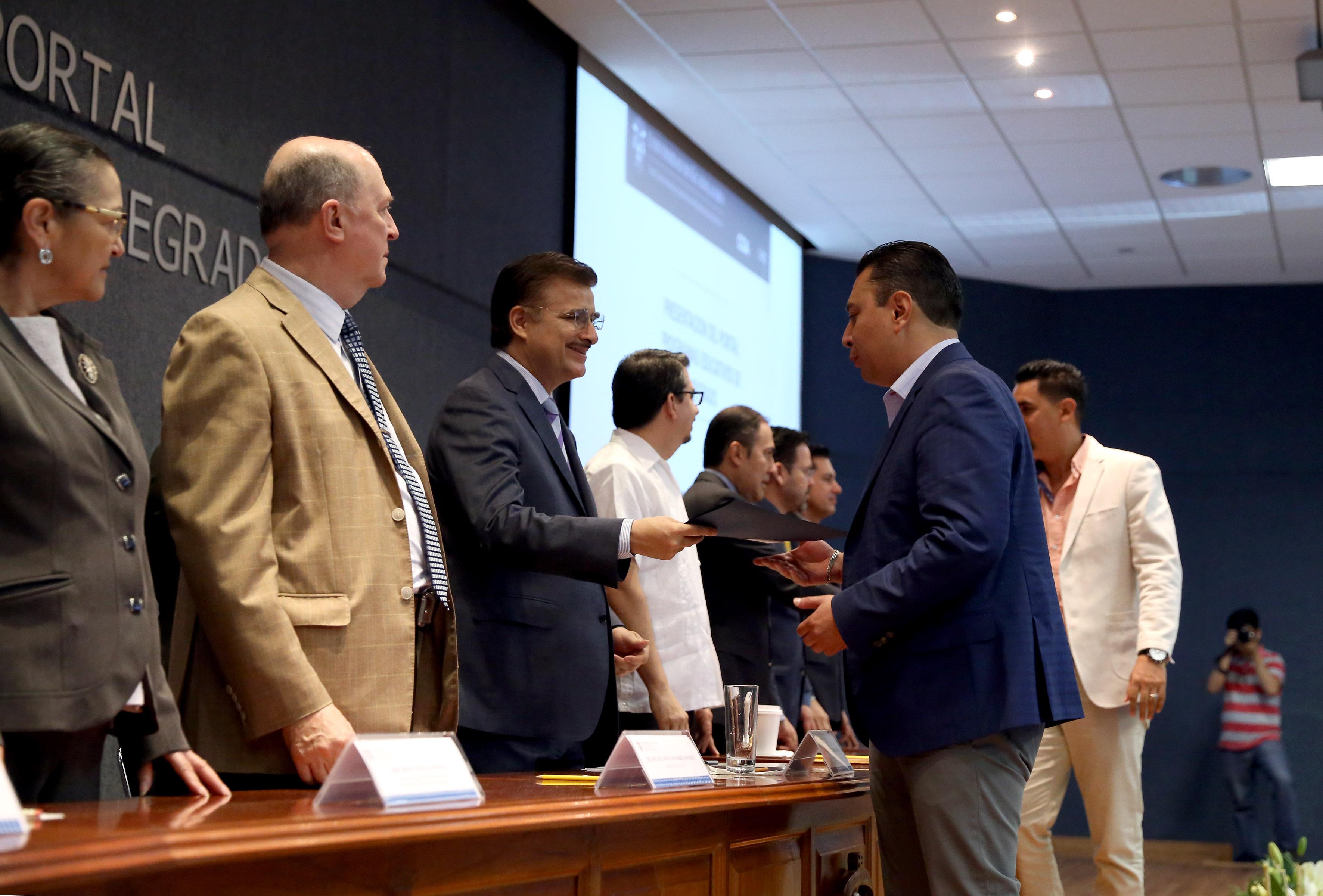 Rector General de la UdeG, maestro Itzcóatl Tonatiuh Bravo Padilla, entregando documento a académico, durante inicio del 2° diplomado en gestión educativa.