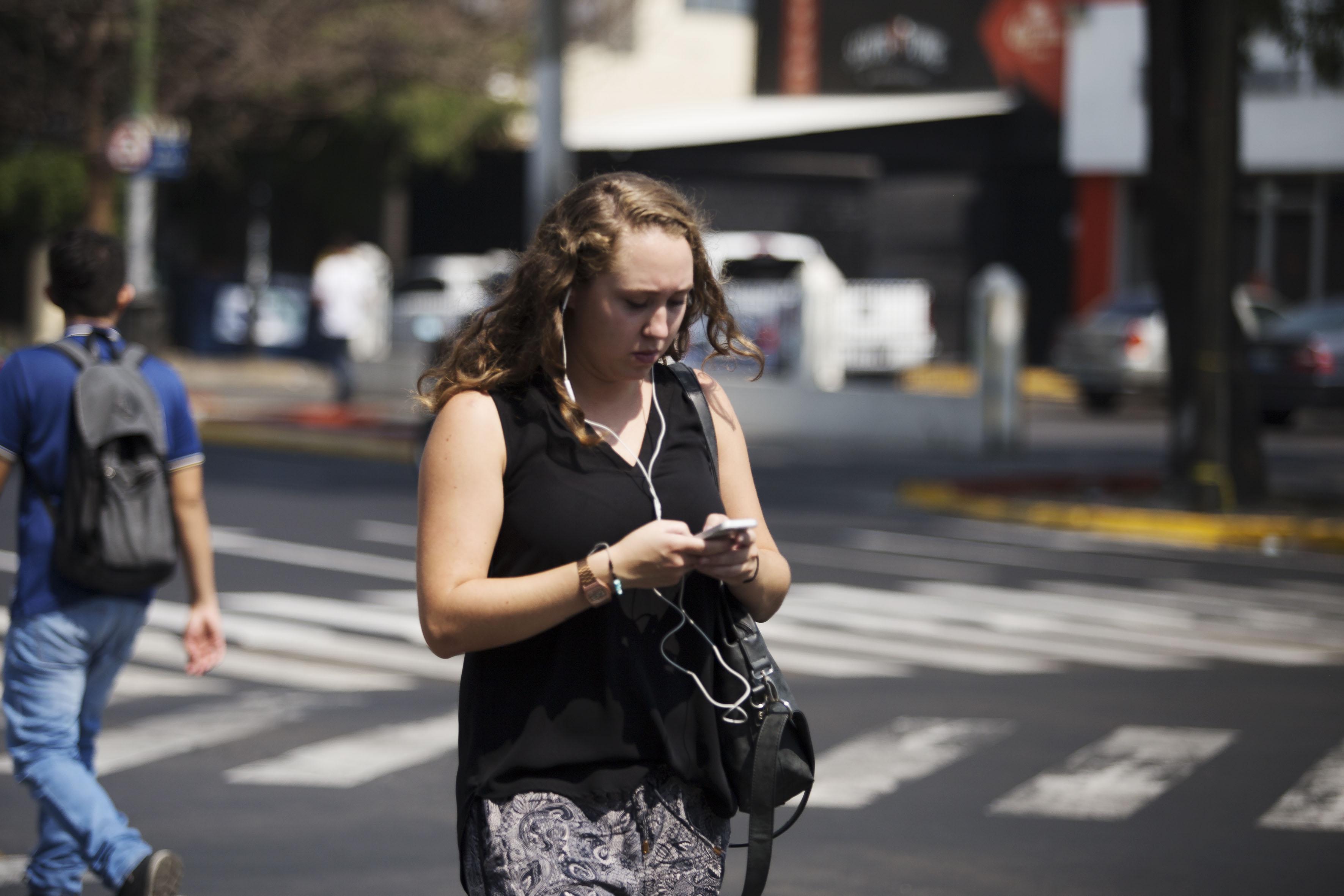 Mujer caminando por la calle, con audífonos y utilizando su teléfono celular.