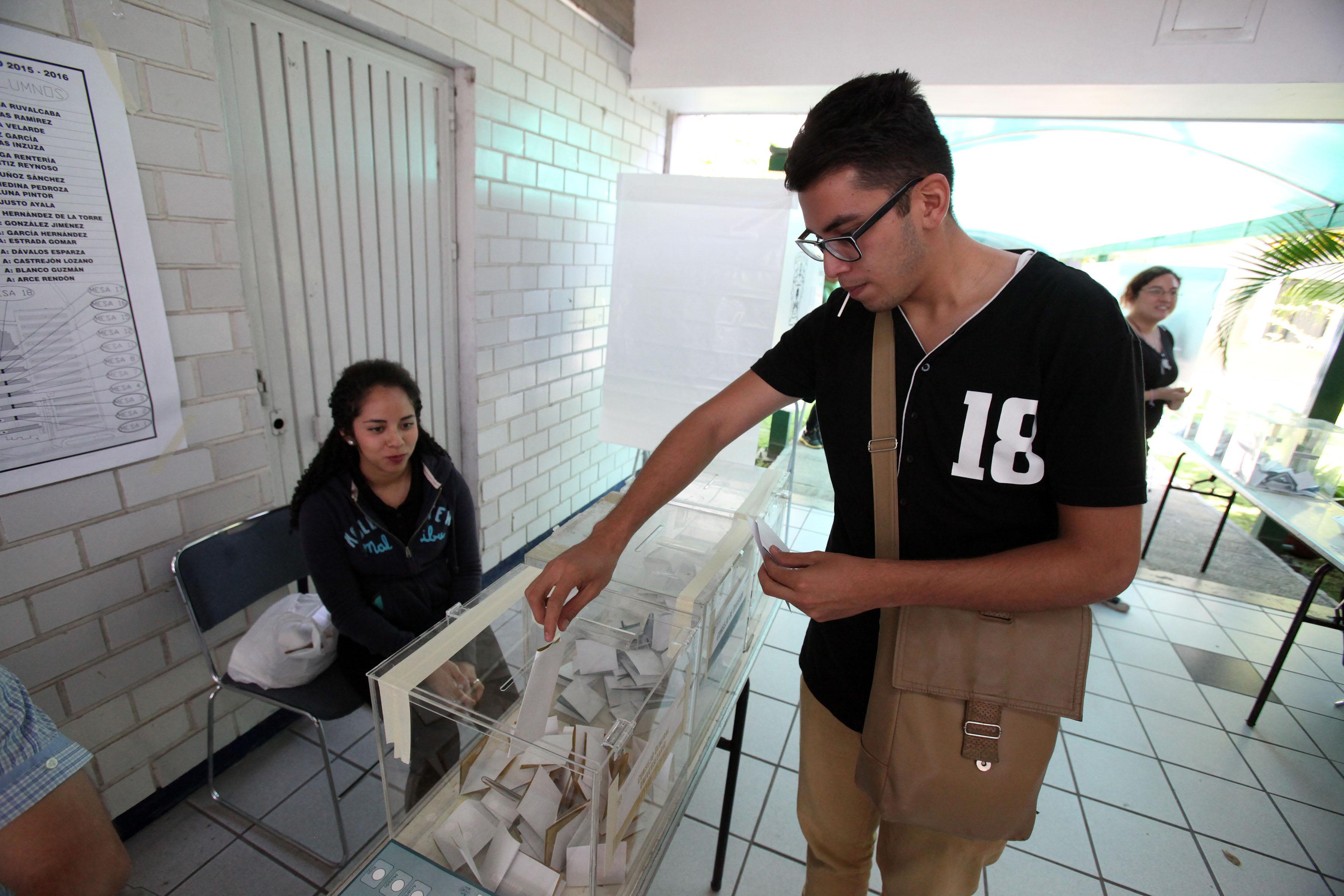 Ciudadano colocando sus votos en la urna, durante el proceso de votación.