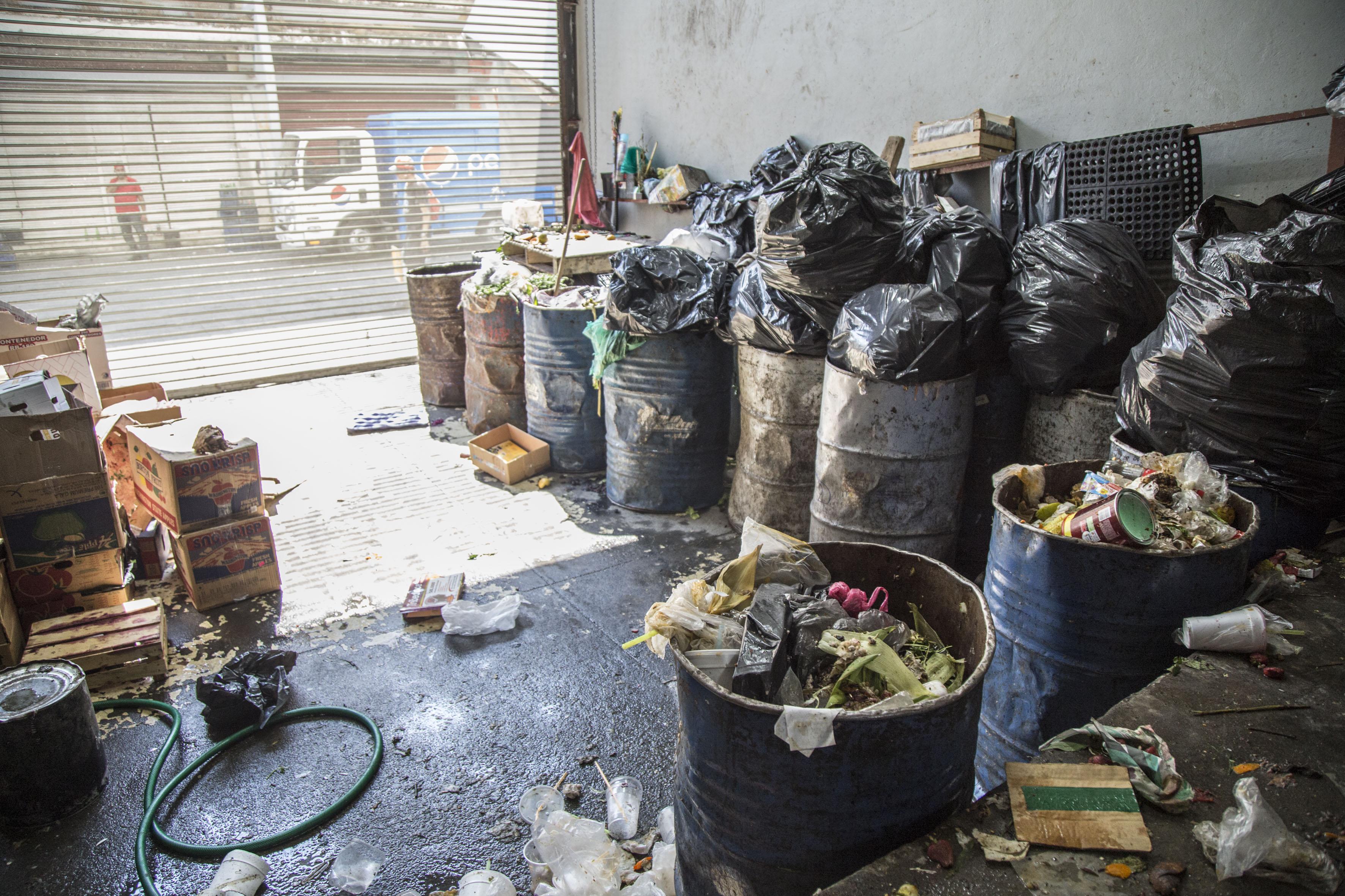 Bodega llena de cajas, botes y bolsas con basura.