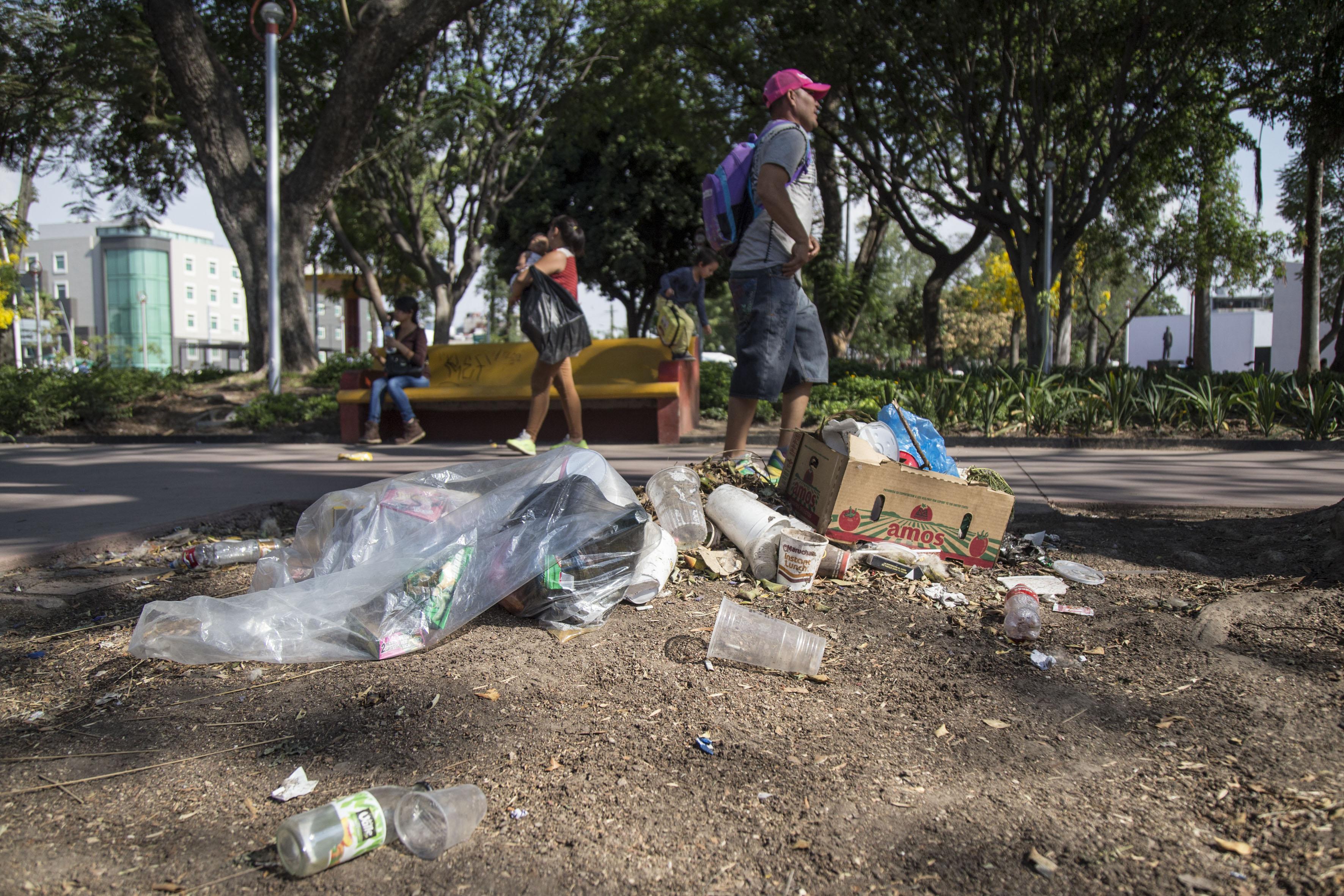 Fracción del Parque Revolución con cajas y bolsas de basura.