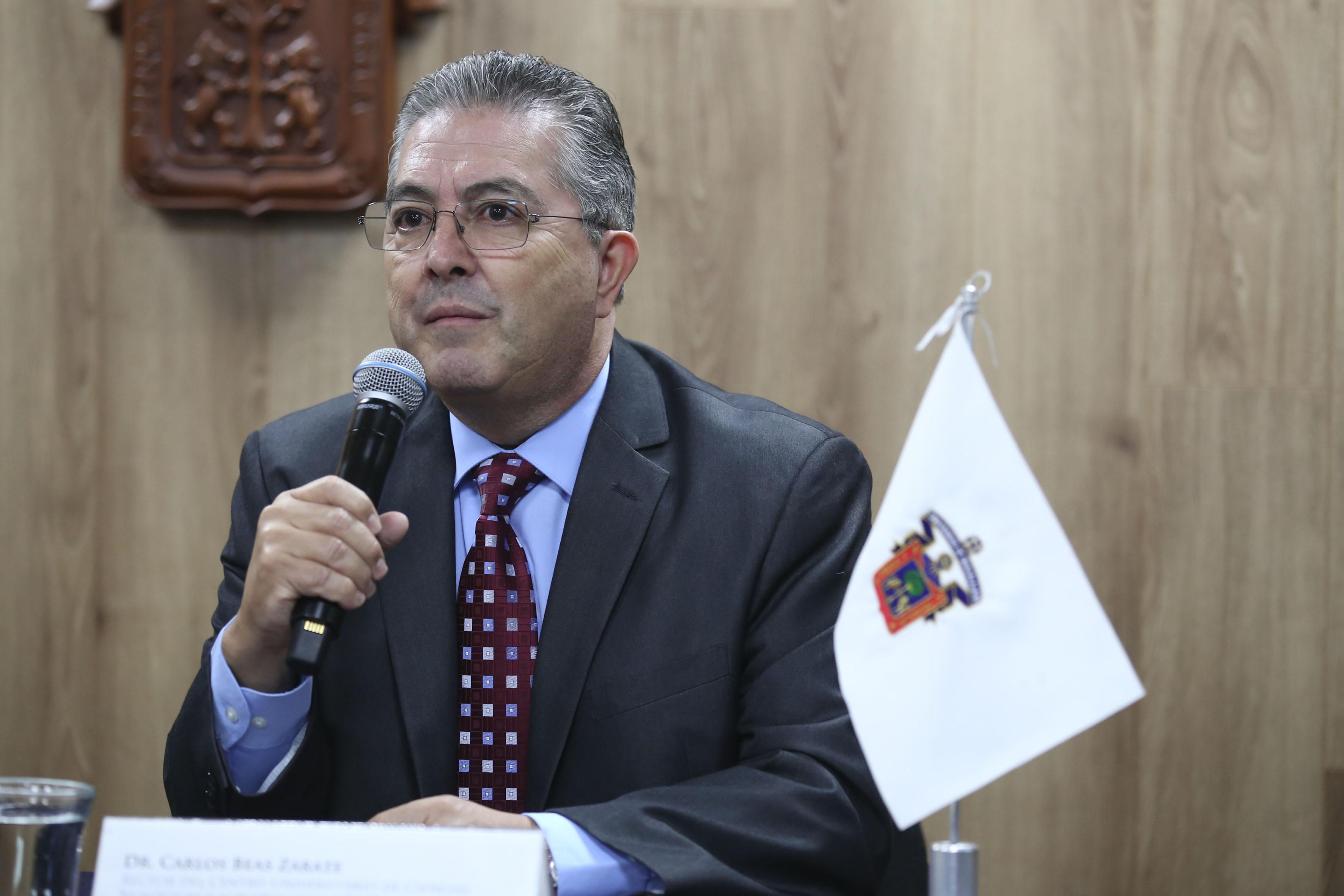 Doctor Carlos Beas Zárate, Rector del Centro Universitario de Ciencias Biológicas y Agropecuarias (CUCBA), con micrófono en mano, haciendo uso de la voz.