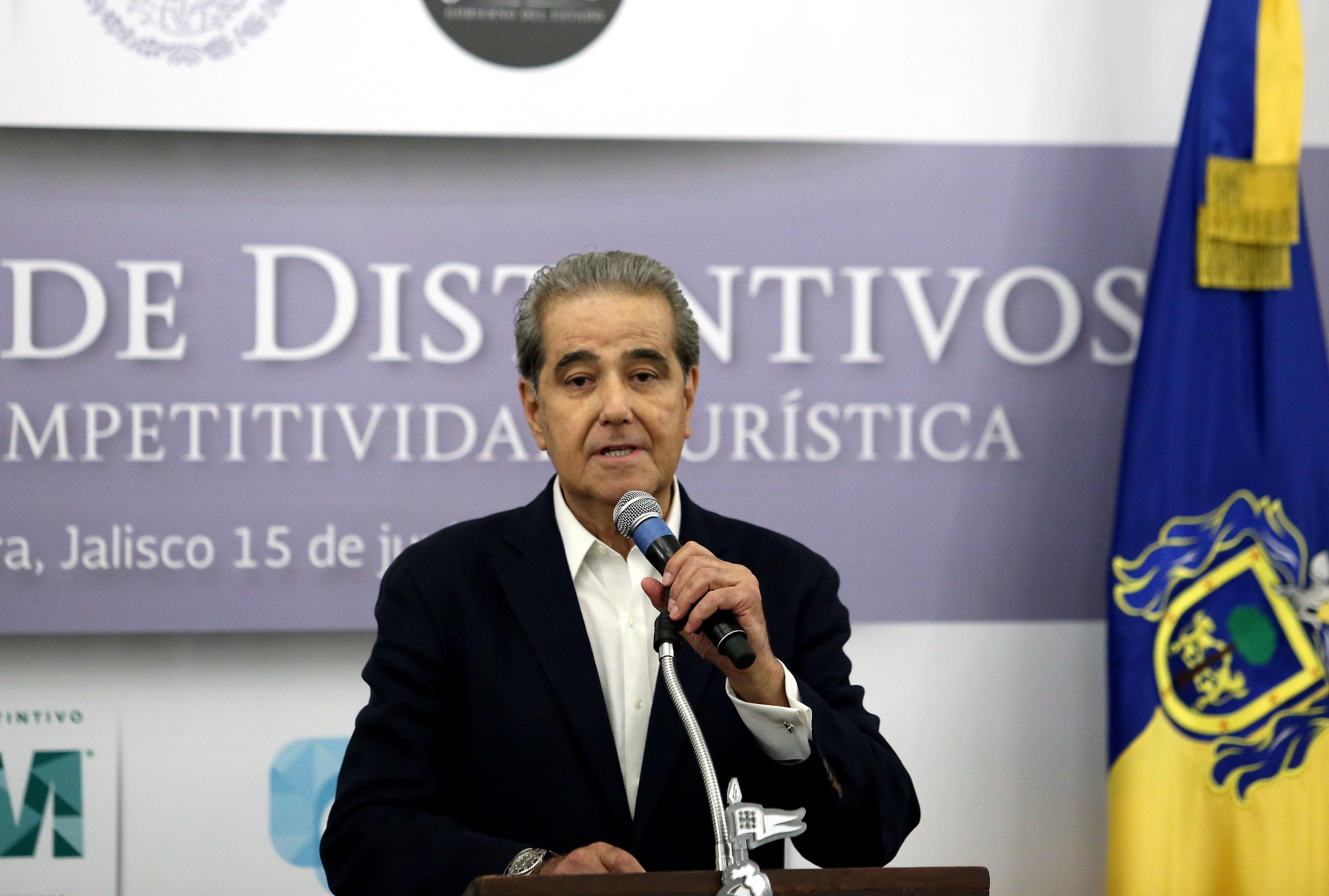 Licenciado Jesús Enrique Ramos Flores, secretario de Turismo de Jalisco, con micrófono en mano, haciendo uso de la voz.