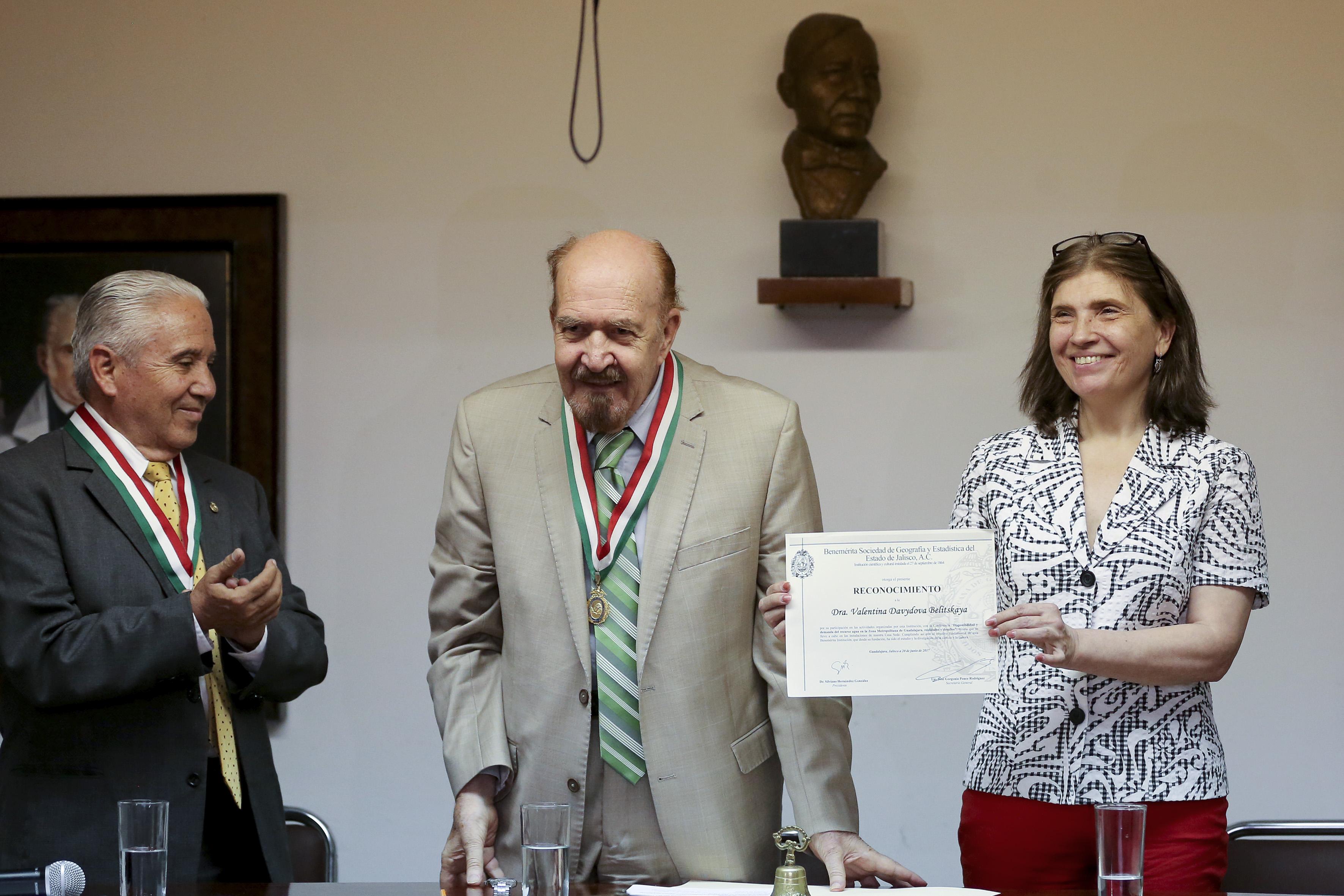 Doctora Valentina Davydova Belitskaya, investigadora del Departamento de Ciencias Ambientales, del Centro Universitario de Ciencias Biológicas y Agropecuarias de la Universidad de Guadalajara, recibiendo un reconocimiento por parte del titular de la Benemérita Sociedad de Geografía y Estadística del Estado de Jalisco, AC.