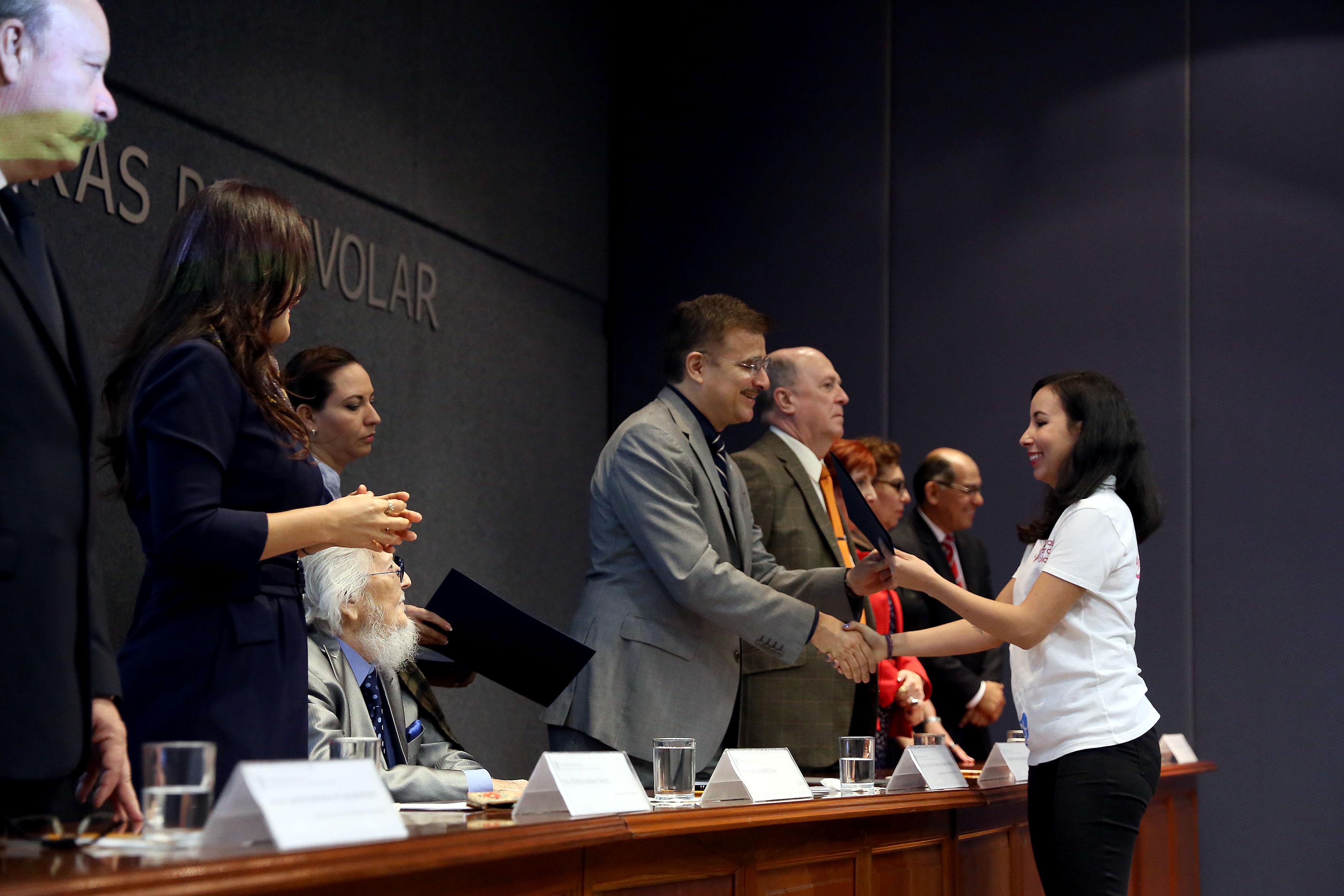 Rector General de la Universidad de Guadalajara, maestro Itzcóatl Tonatiuh Bravo Padilla, otorgando reconocimiento a personal participante en el programa de letras para volar.