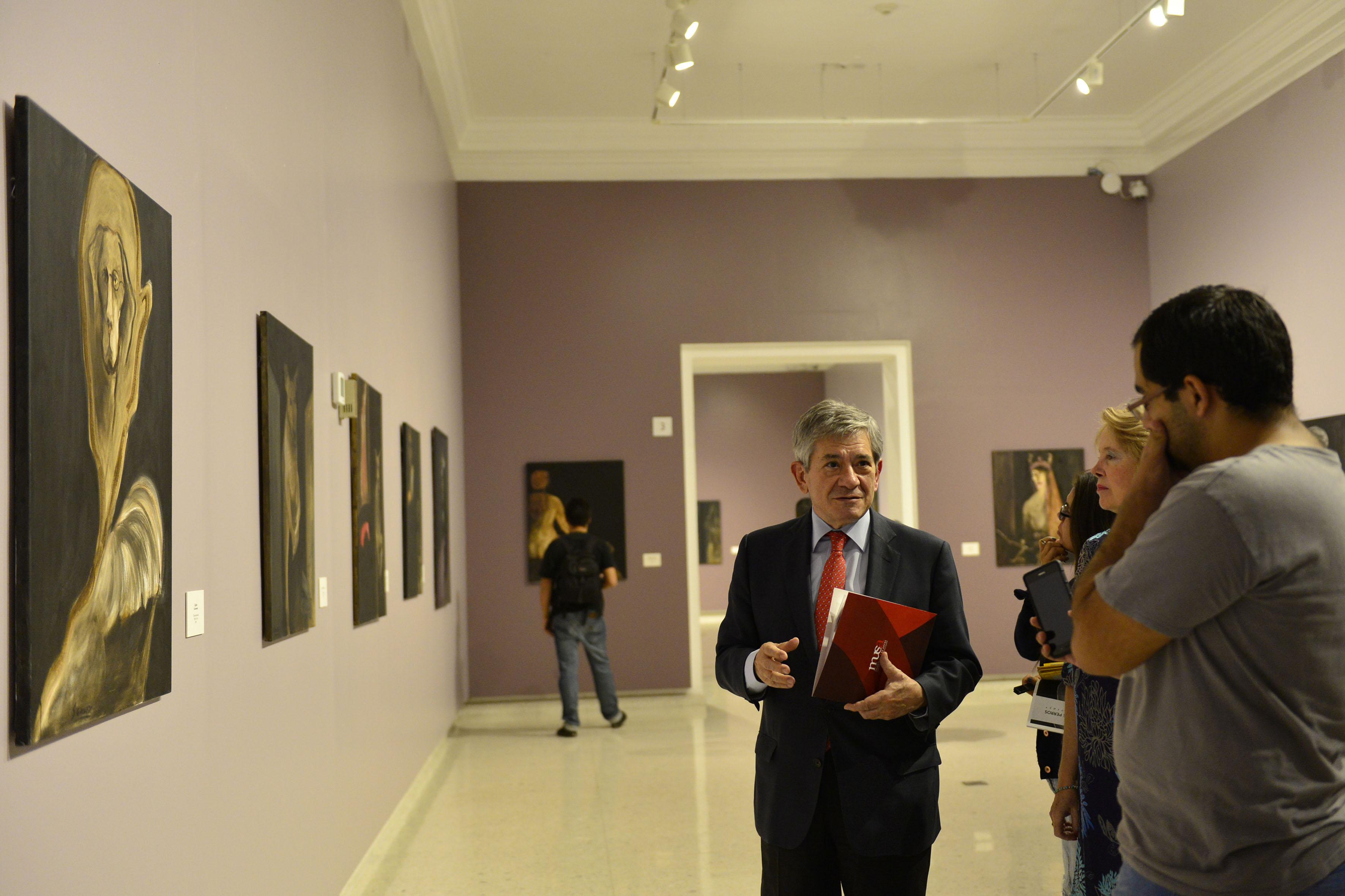 Viudo de la pintora, Enrique Barón Crespo, dando a conocer la exposición: Coloquio de Perros; a reporteros de la prensa, durante recorrido a los salones del Musa.