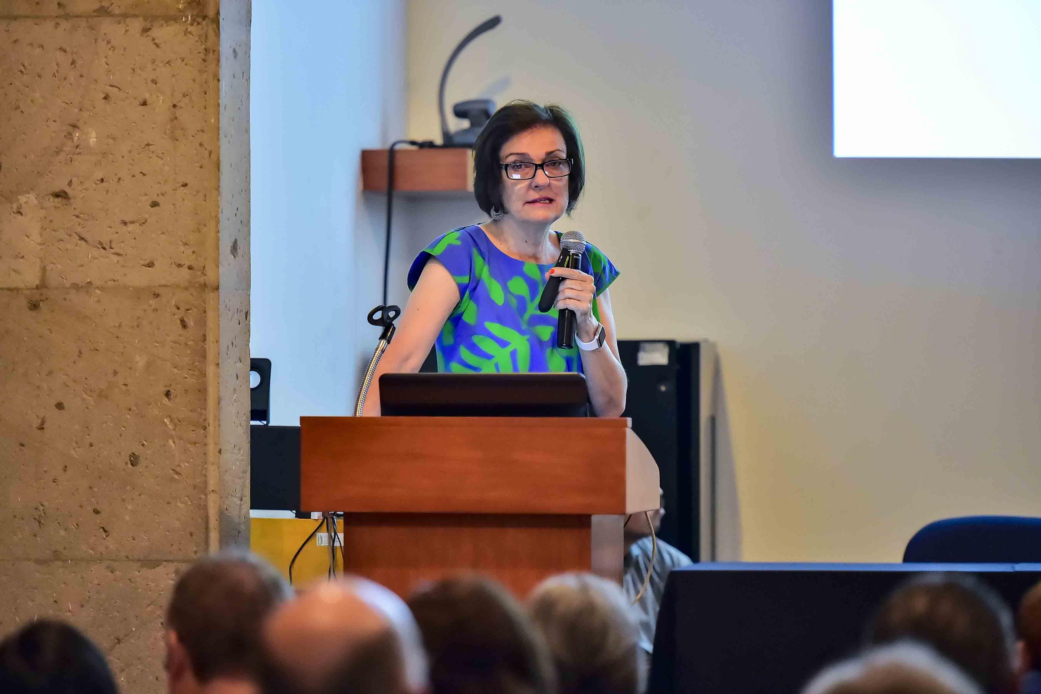 Directora del Instituto de Neurociencias (Ineuro), de la Universidad de Guadalajara, doctora Esmeralda Matute Villaseñor, con micrófono en mano, haciendo uso de la palabra, durante su conferencia.