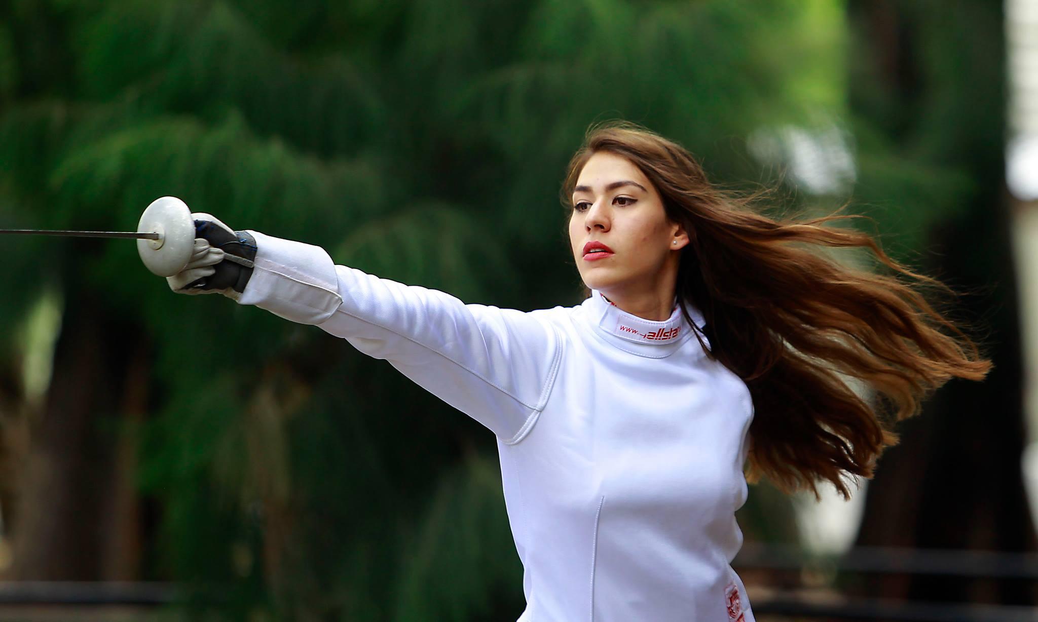 Alely Hernández, esgrimista y estudiante del CUCEA, en posición de defensa con florete, durante entrenamiento en jardines del centro universitario.