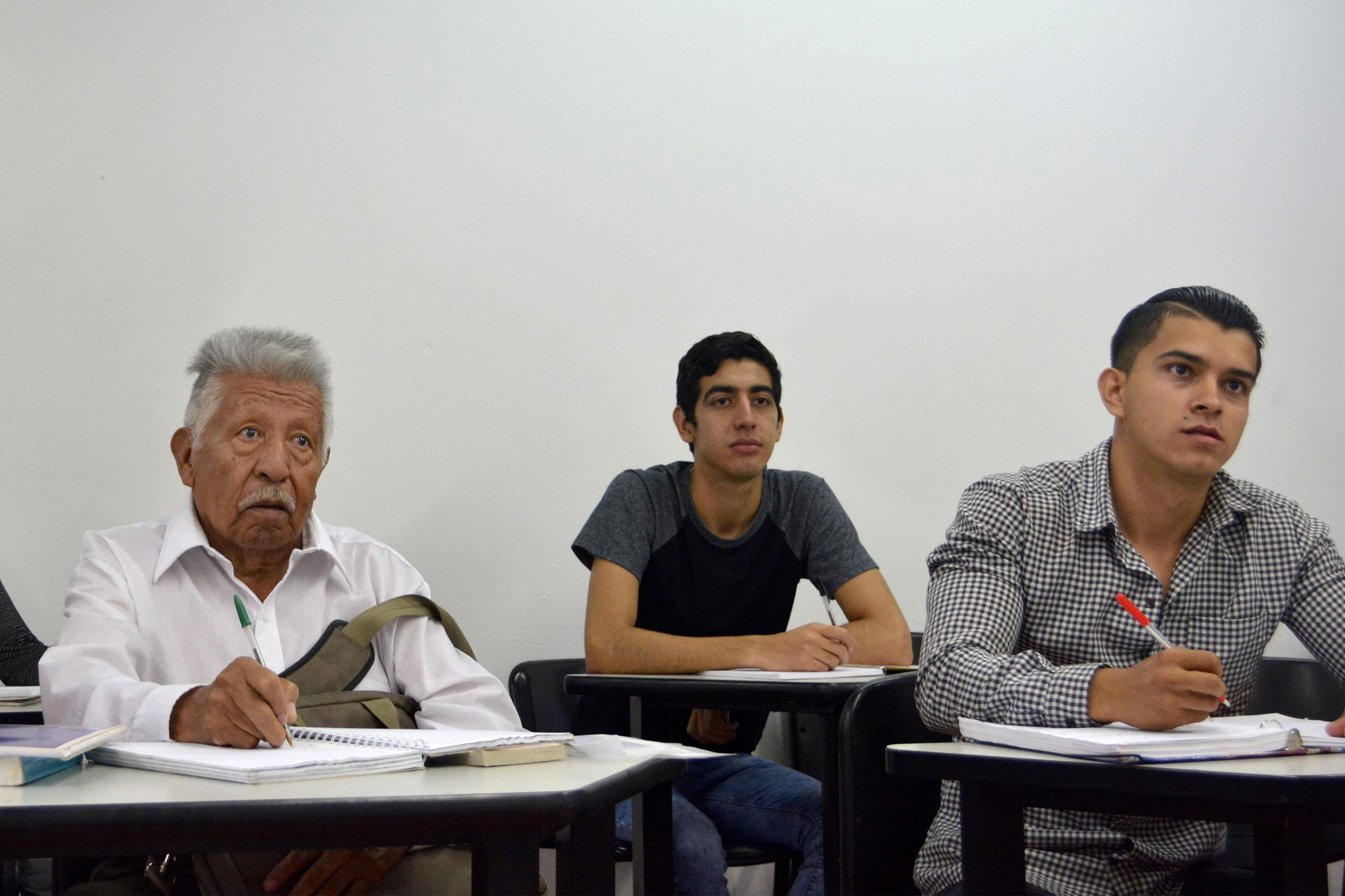 José Mejía Peralta estudiante longevo de la carrera de abogado, tomando notas, durante inicio de clases en la UdeG