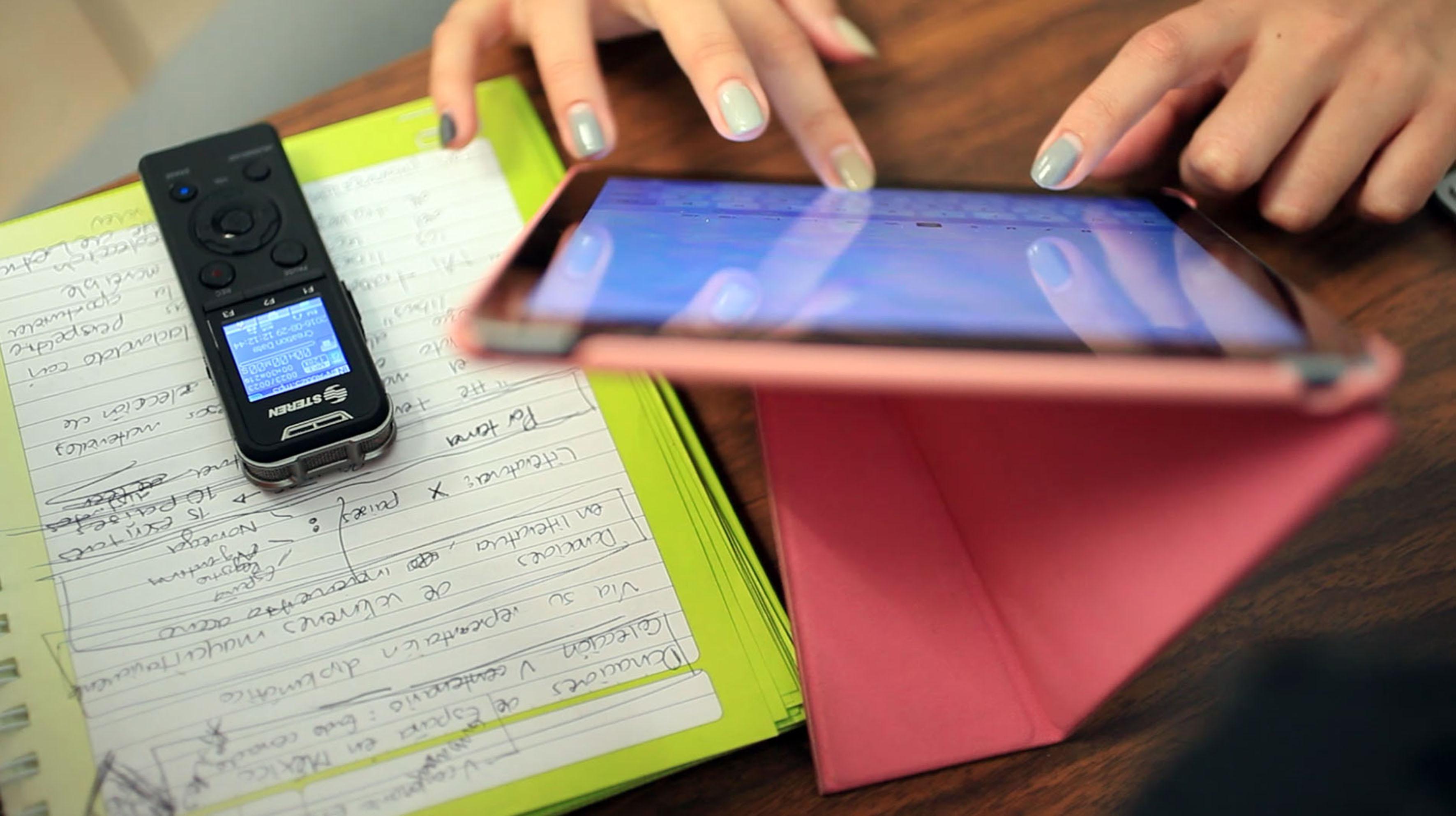 periodista documentando con tableta rosa y documentacion de audios