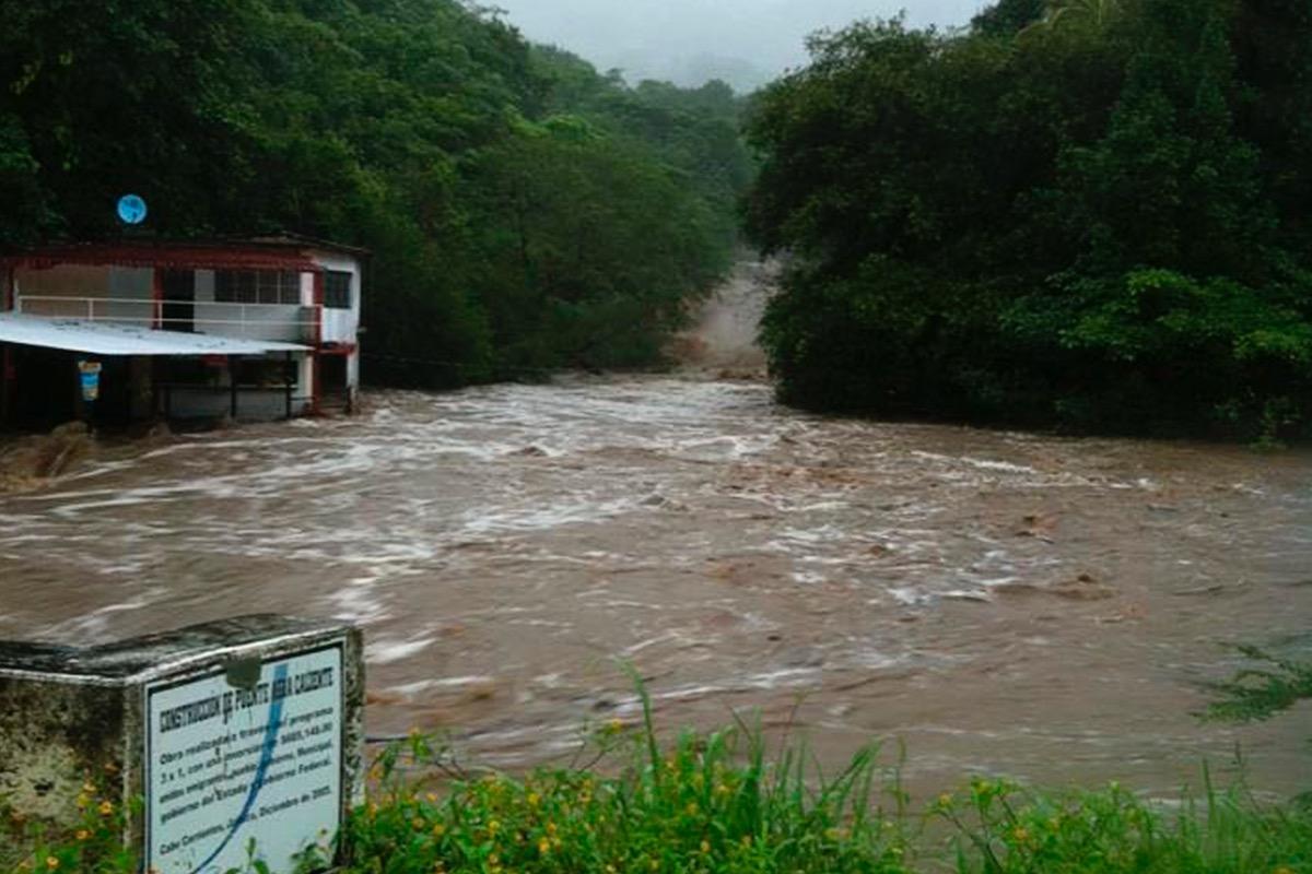 Camino y carretera con cauce de rios de agua lodada a causa de la inundación por lluvias.