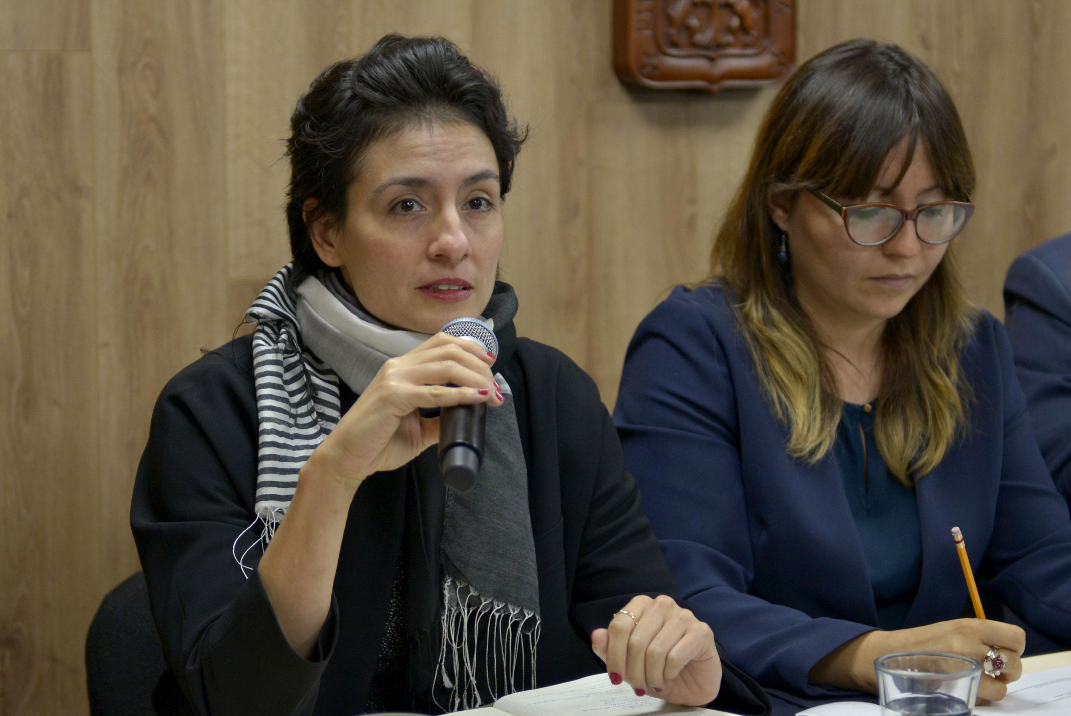 Maestra Melissa Amezcua, especialista de estudios políticos del CUCSH, con micrófono en mano haciendo uso de la palabra, durante rueda de prensa.