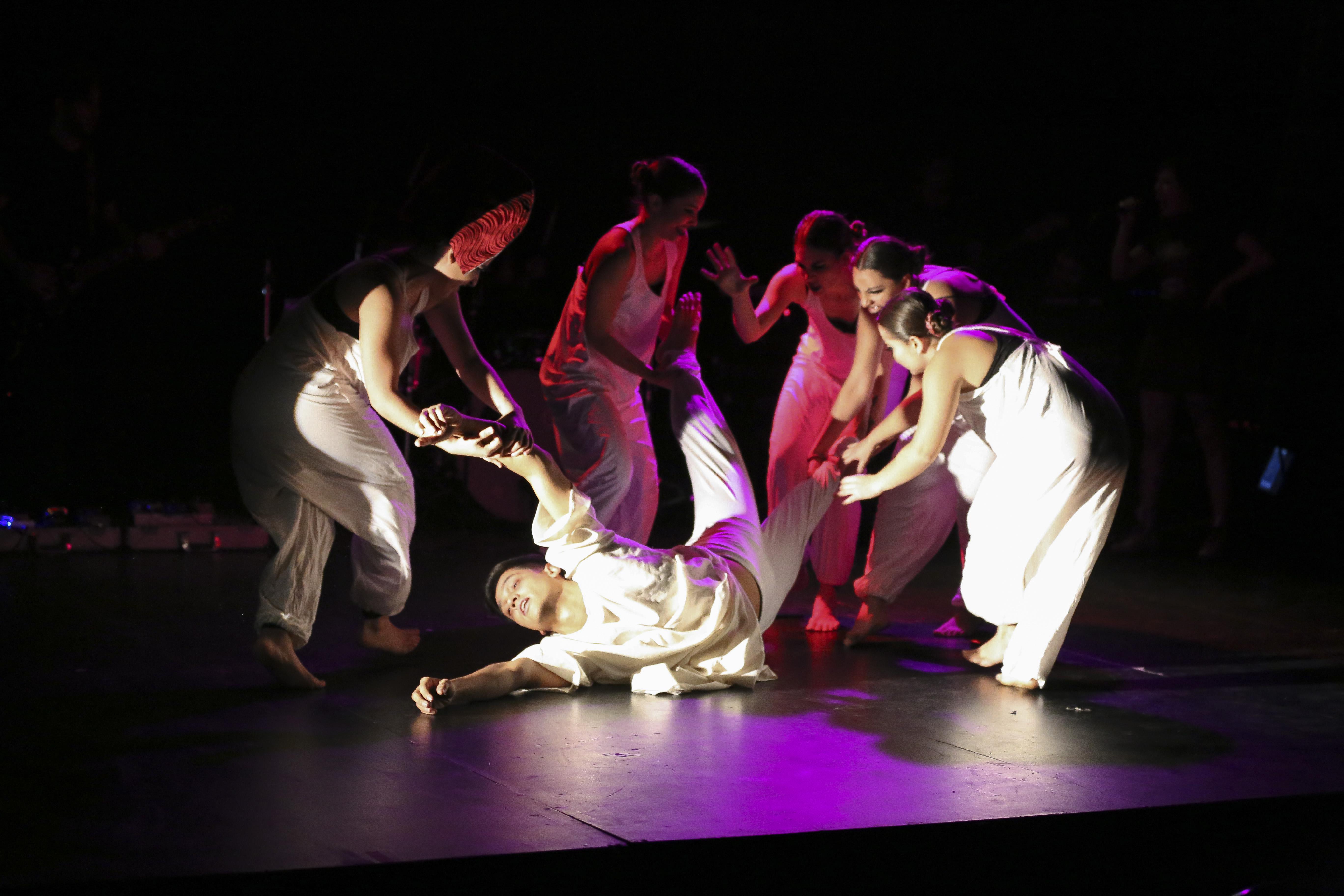 Actores en escena, realizando una obra de teatro; en donde dentro de sus personajes, cinco mujeres se encuentran arrastrando y jalando a un hombre de las piernas y brazos.