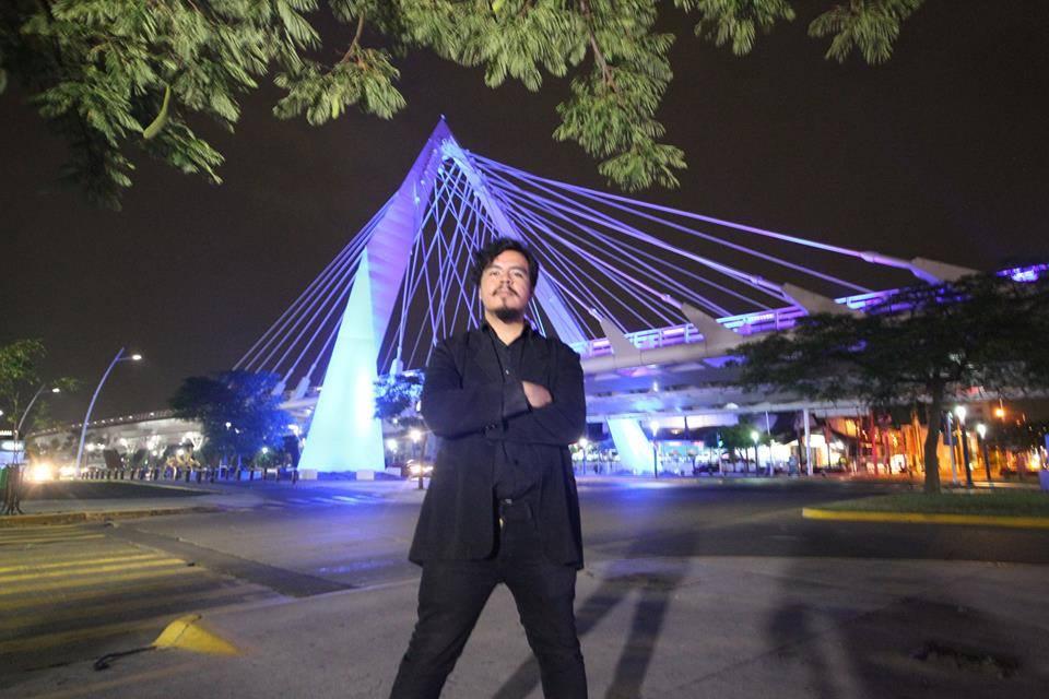 Fernando García Sandoval, egresado de la licenciatura en Gestión Cultural de UDGVirtual. Parado enfrente del puente tirantado de la Ciudad de Guadalajara.