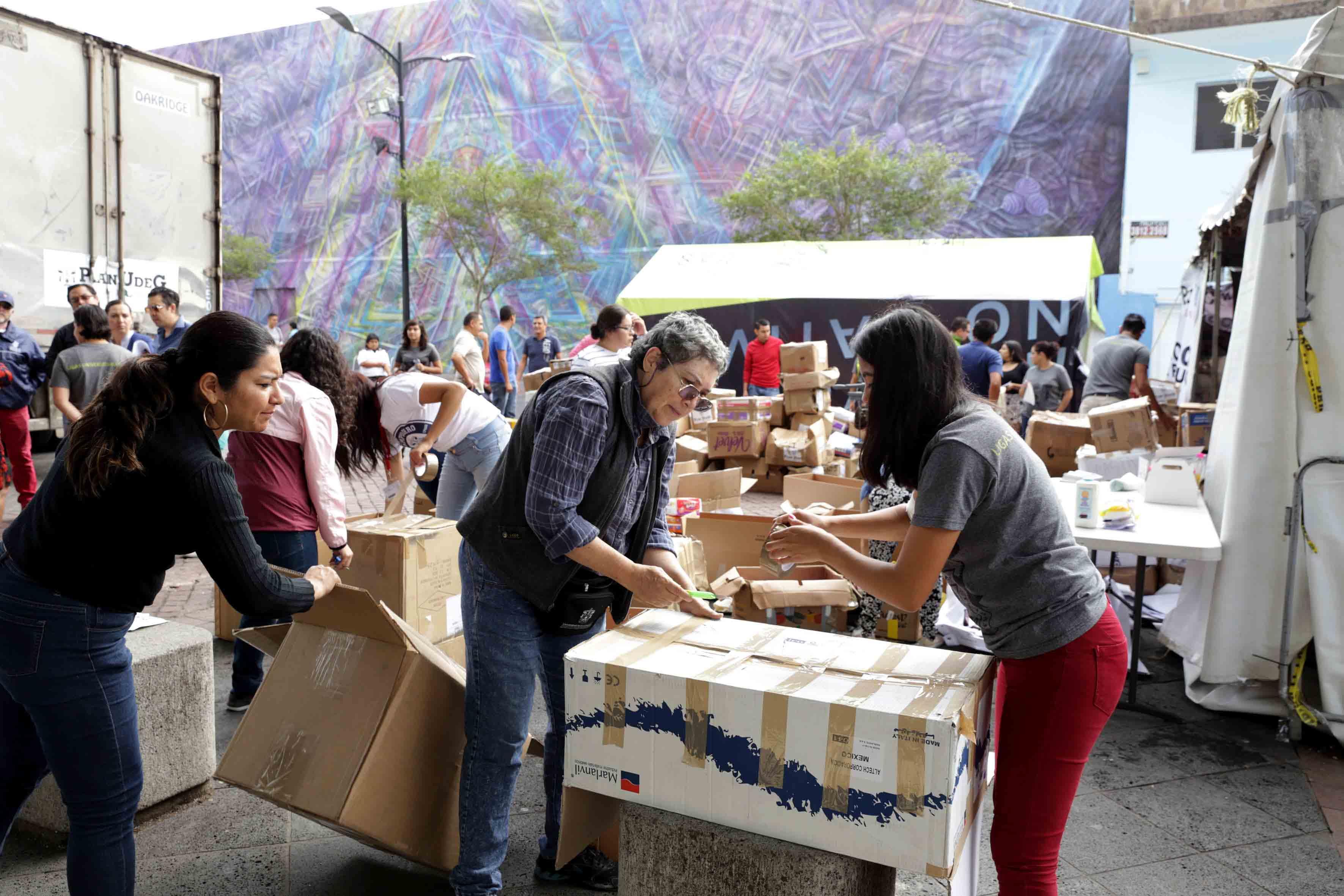 Voluntarios armando cajas con los víveres donados