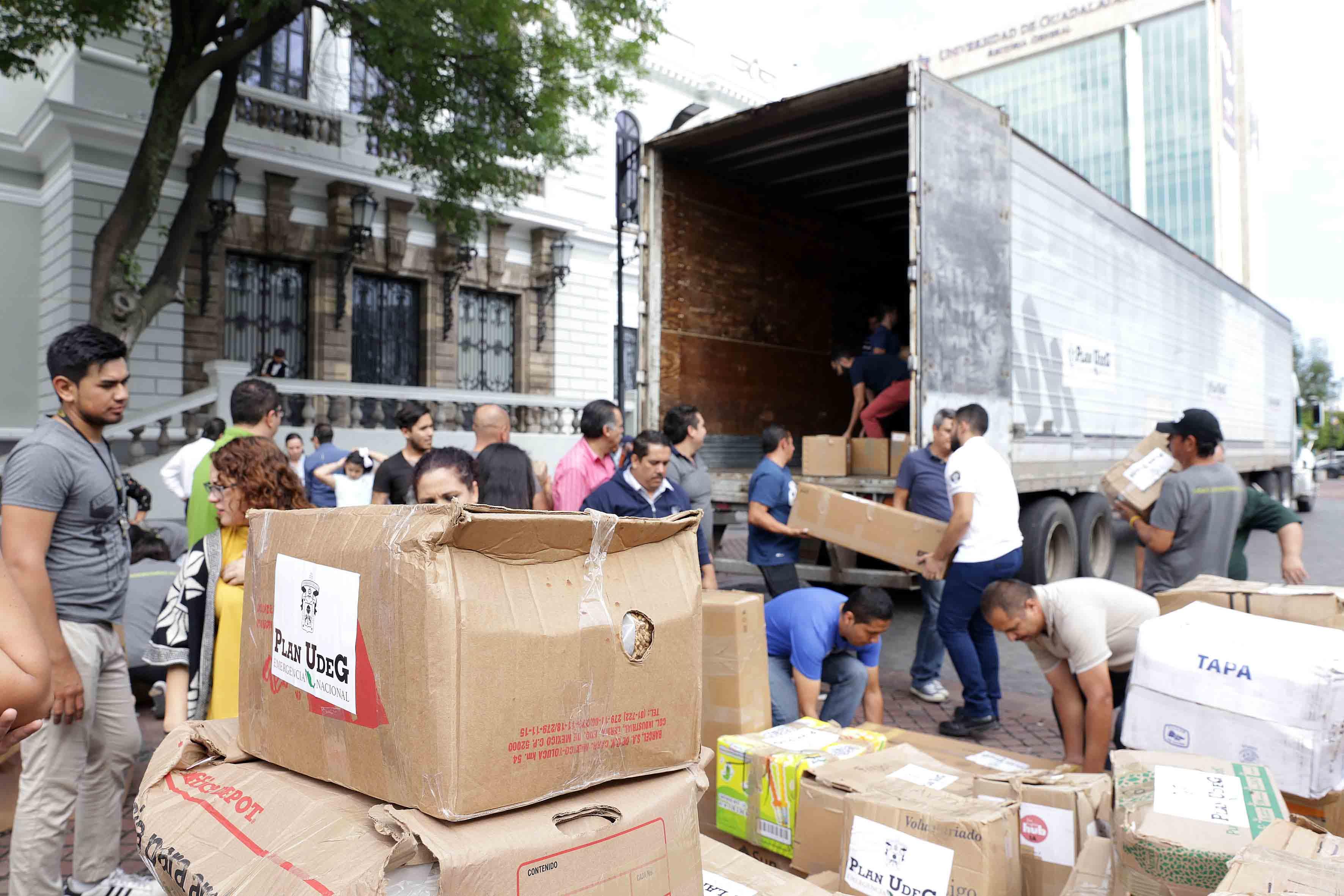 Voluntarios cargando cajas para llenar los contenedores