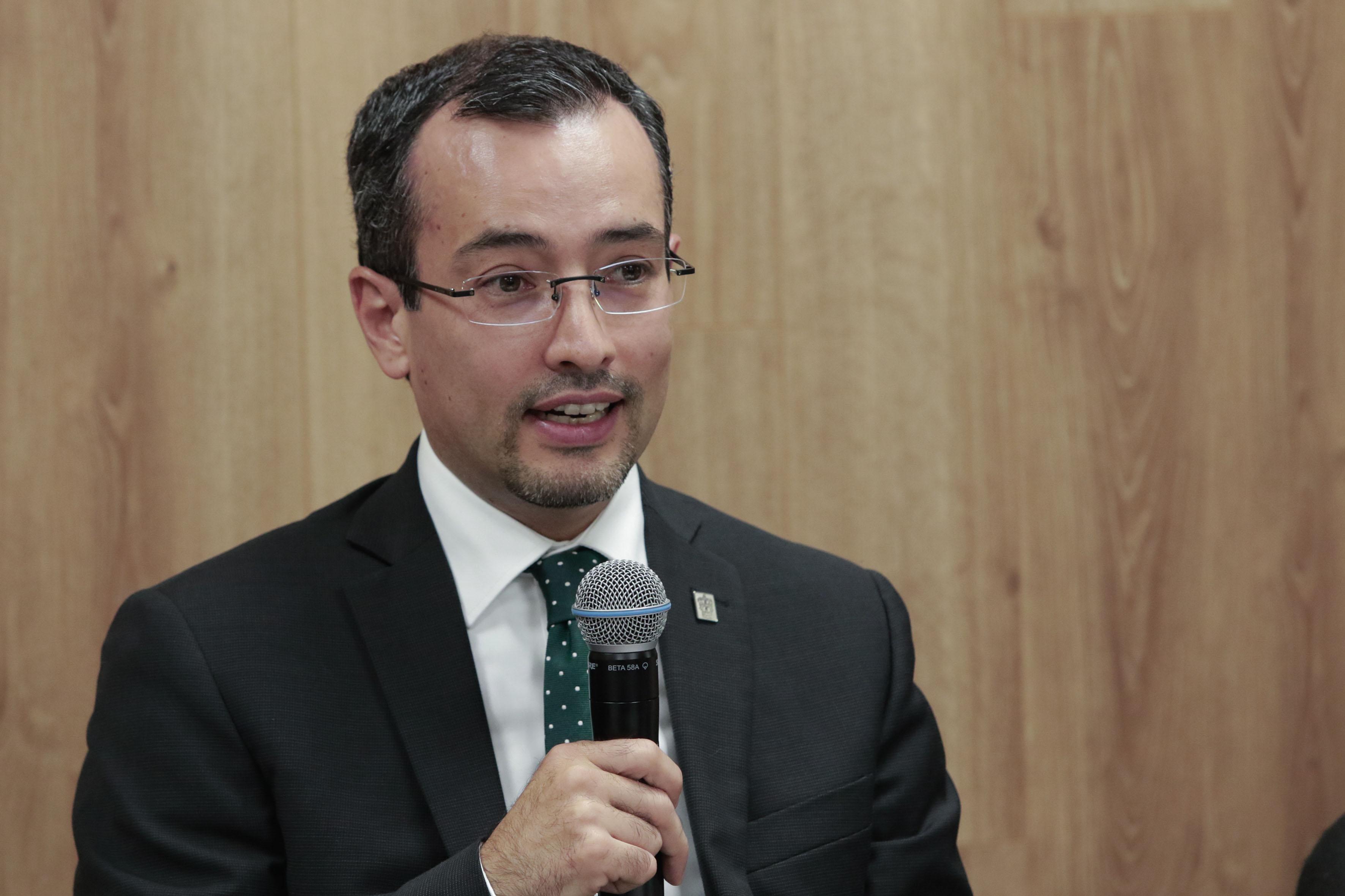 Doctor Carlos Iván Moreno Arellano, coordinador general de Cooperación e Internacionalización, con micrófono en mano, haciendo uso de la voz.