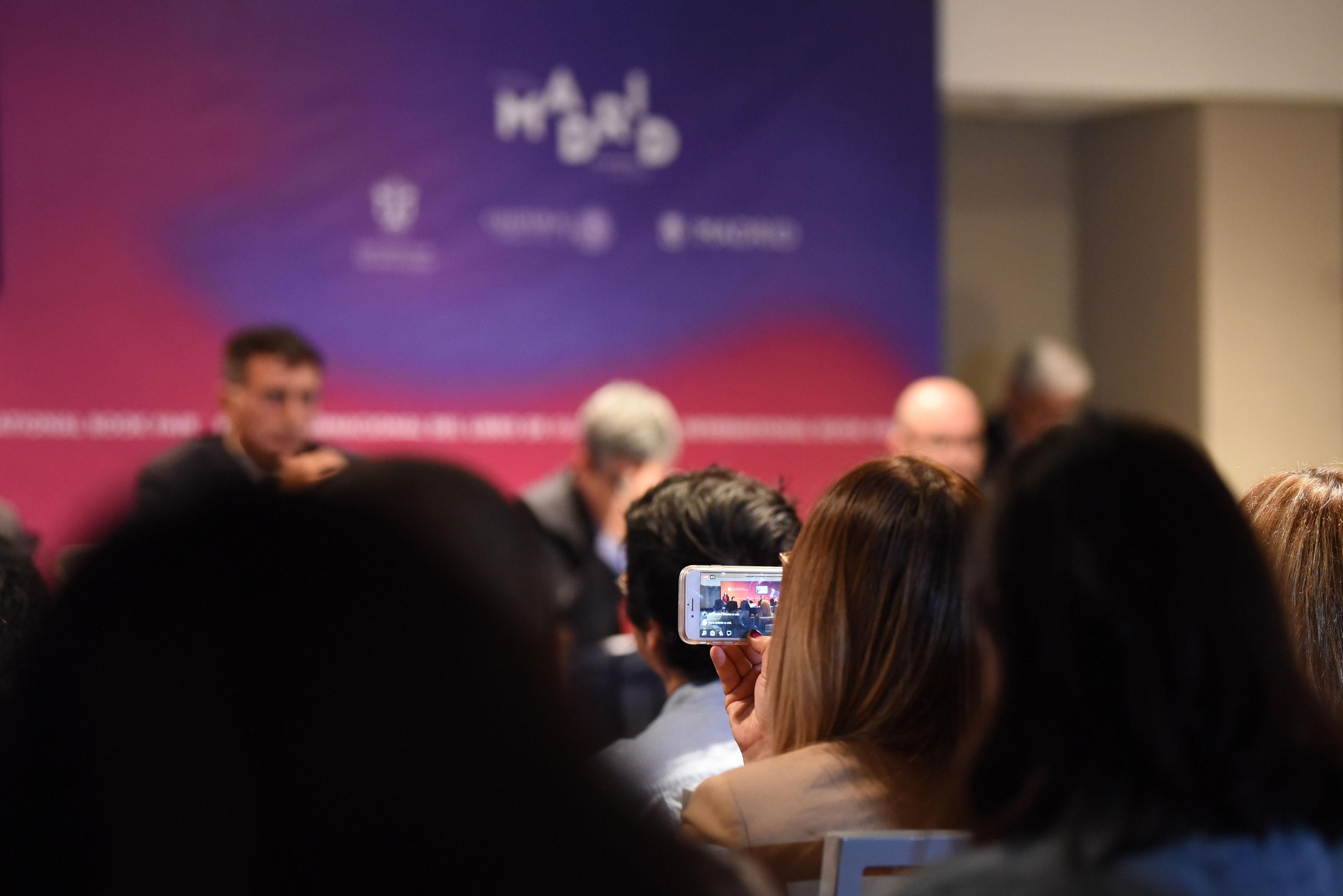 Asistente a la ceremonia, grabando vídeo del evento, con su teléfono celular.