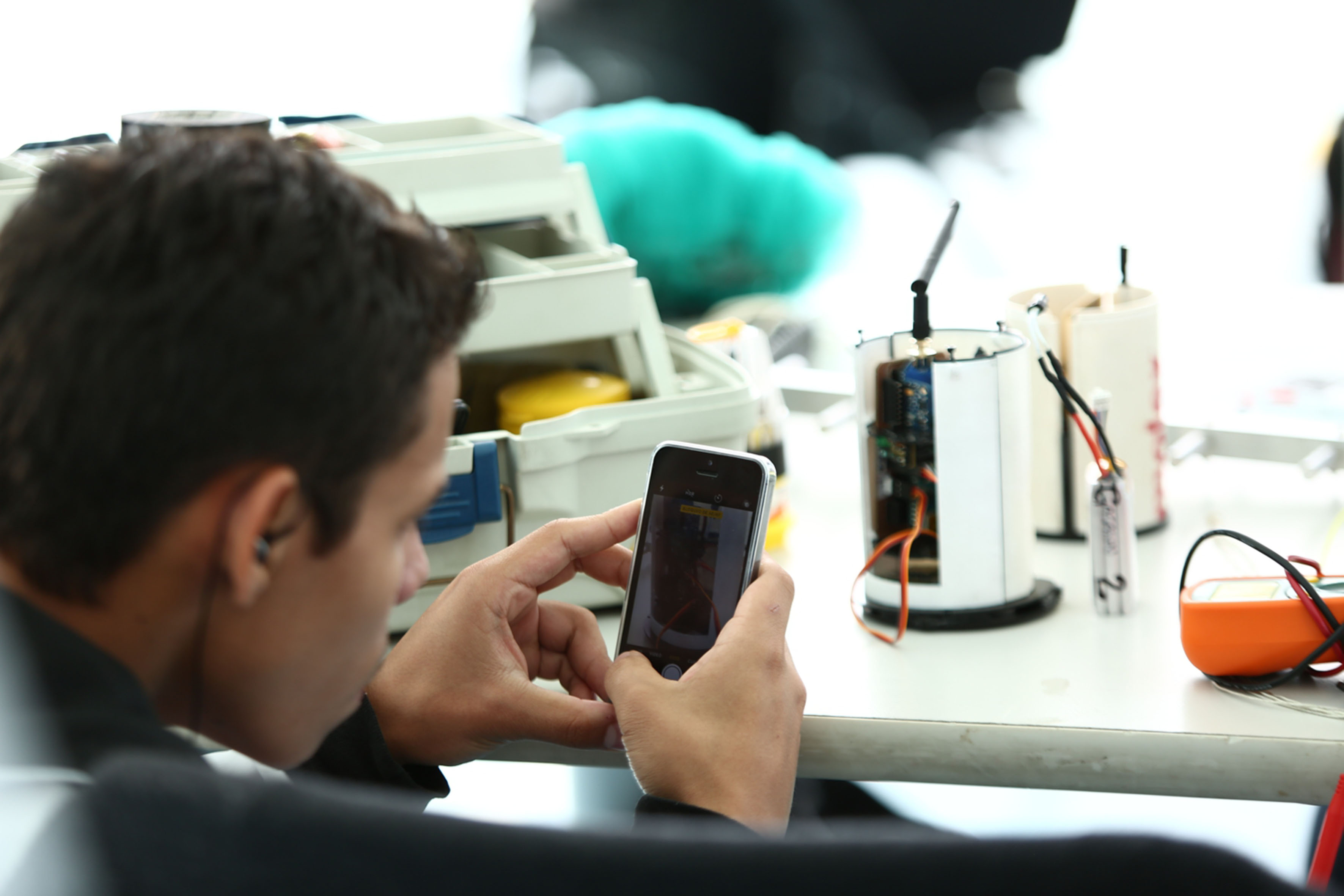 Estudiante de ingeniería, tomando una foto por dentro al prototipo de su satélite en miniatura.