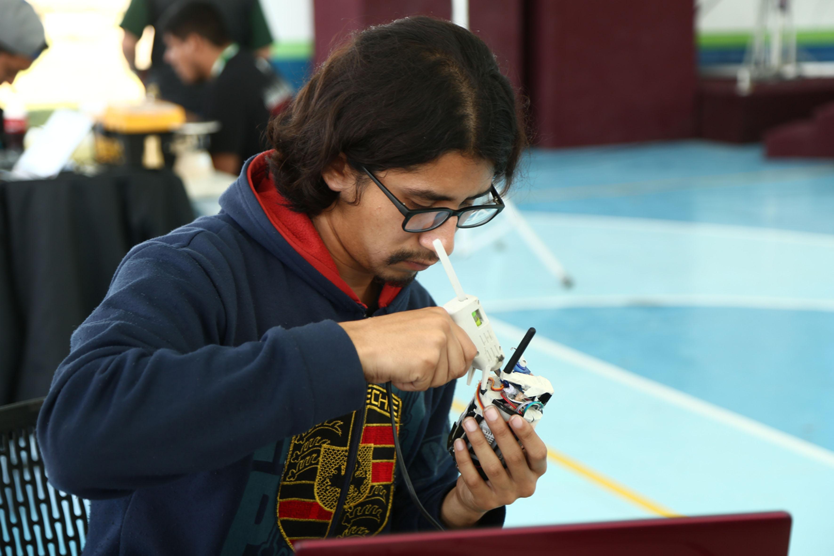 Estudiante de ingeniería pegando piezas a su satélite en miniatura.