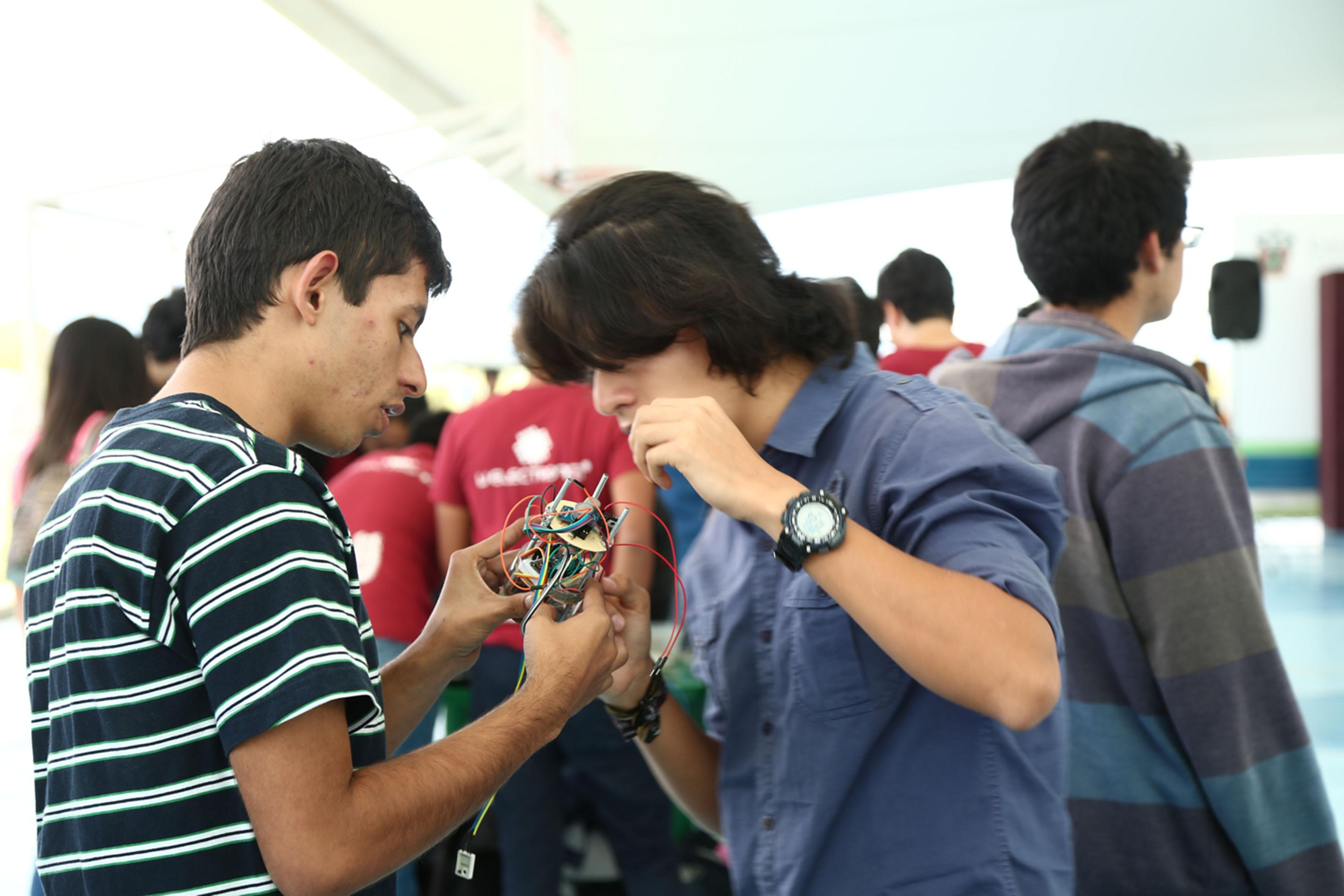 Estudiantes de ingeniería, acomodando los cables y circuitos de su satélite en miniatura.