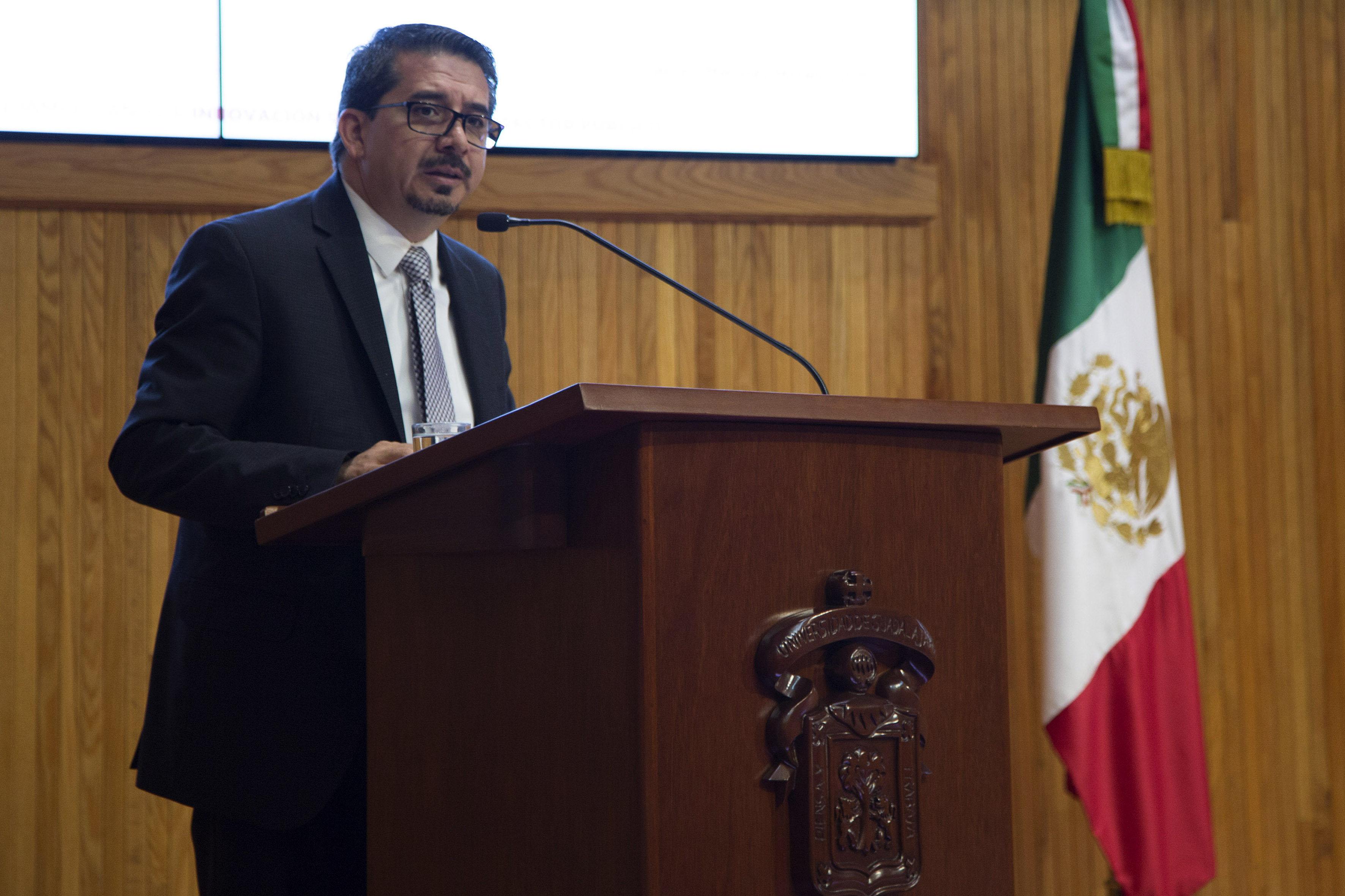 Rector del Centro Universitario de Ciencias Económico Administrativas, maestro José Alberto Castellanos Gutiérrez, en podium de Paraninfo haciendo uso de la palabra.