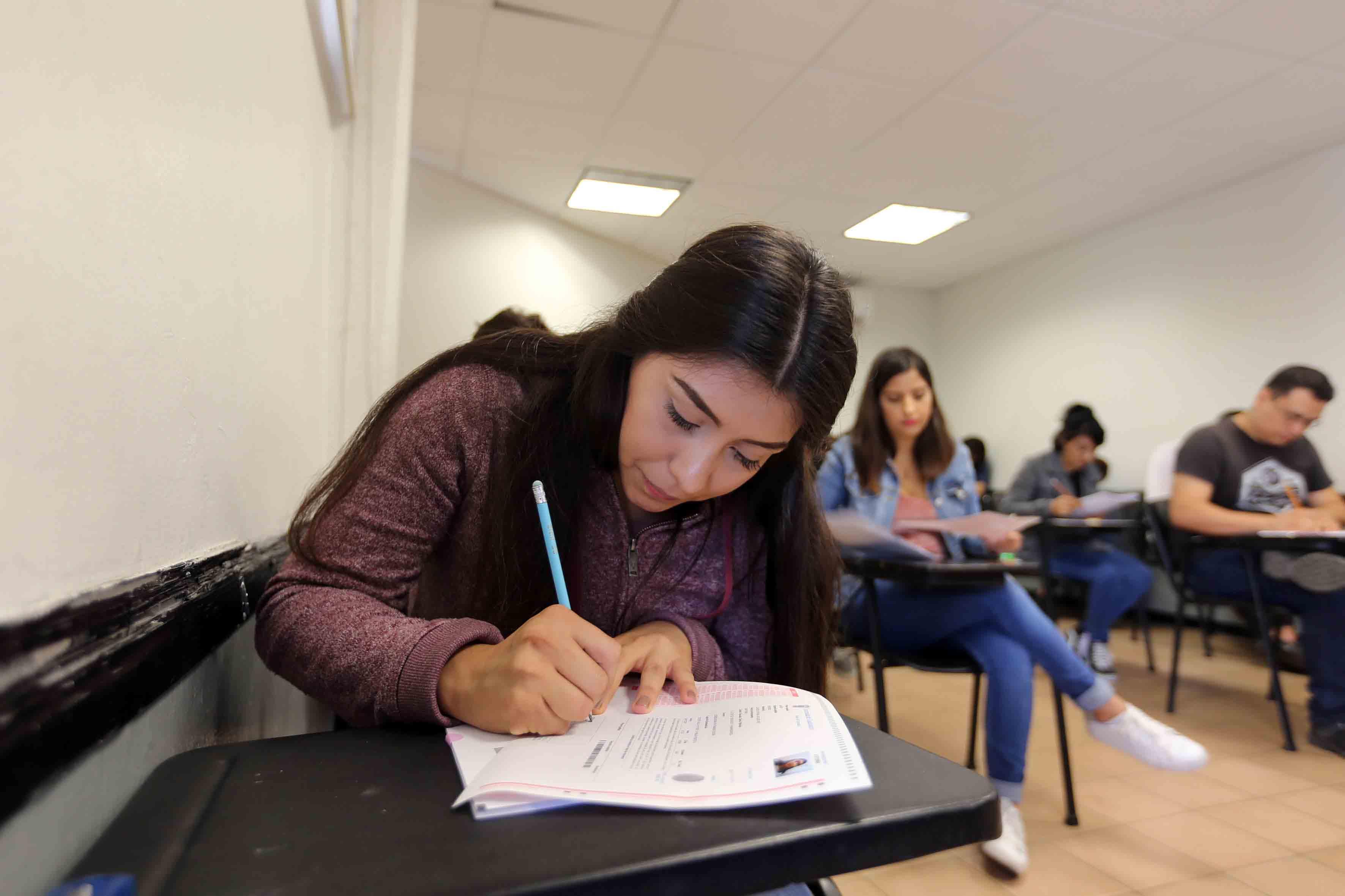 Joven aspirante aplicando examen de admisión para licenciatura de la Universidad de Guadalajara.
