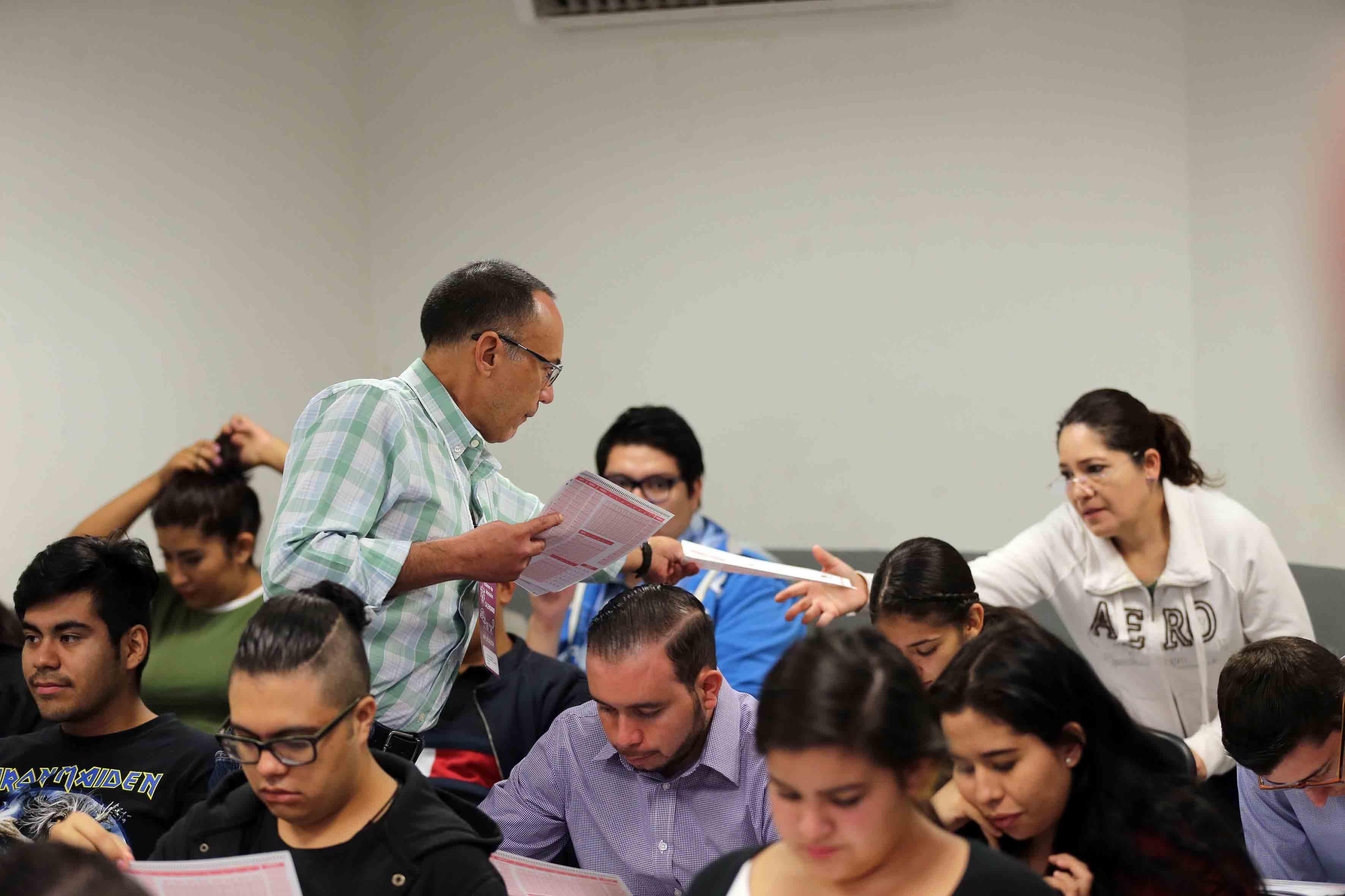 Aplicador de examen de admisión, entregando hojas de respuesta a los aspirantes de licenciatura.