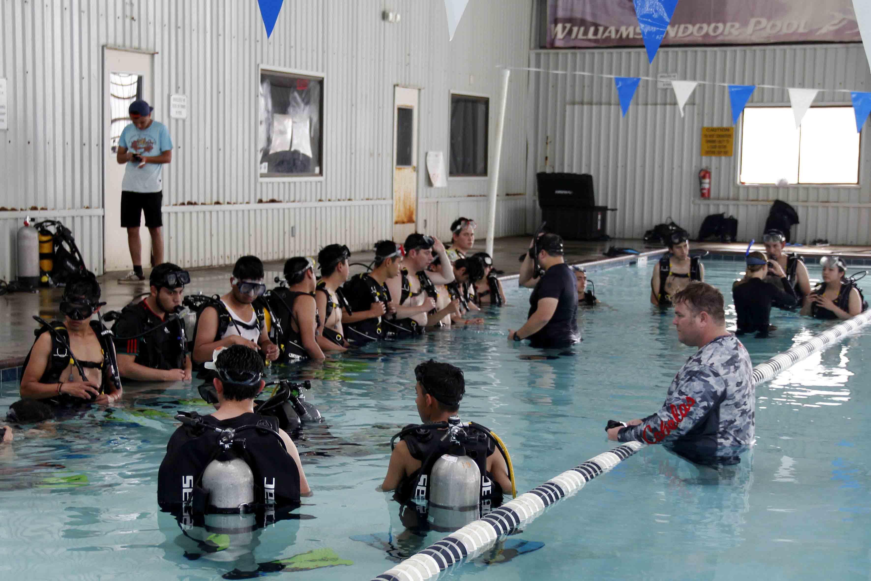 Participantes del International Air and Space Program 201, realizando actividades de buceo, manejo y recolección de herramientas bajo el agua.