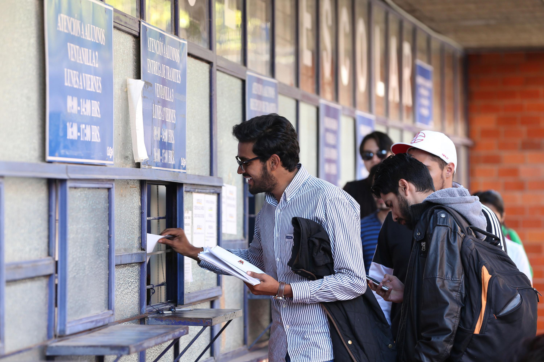 Aspirante haciendo entrega de su documentación en ventanilla del centro universitario.