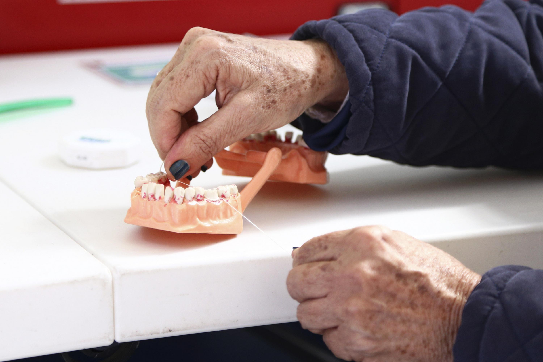 Persona enseñando el uso adecuado del hilo dental.