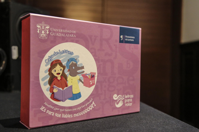 """La """"Caja de Letras"""" es de color rosa pálido con ilustración de jóvenes y animales."""