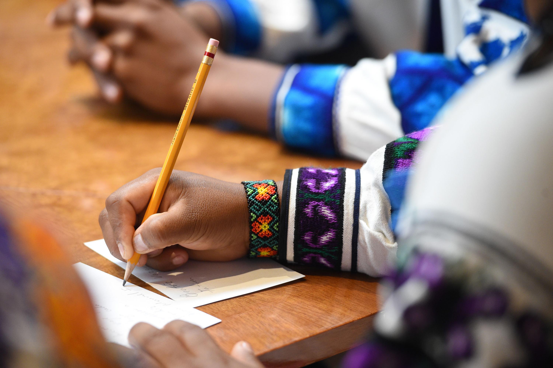 Estudiante Indígena, escribiendo con un lápiz, una nota sobre un pedazo de papel.