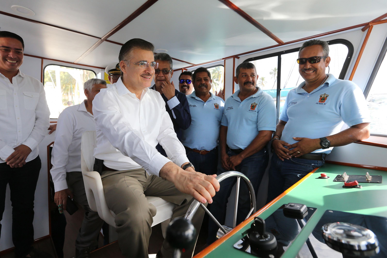 El rector general sentado frente al timón del barco junto a la tripulación