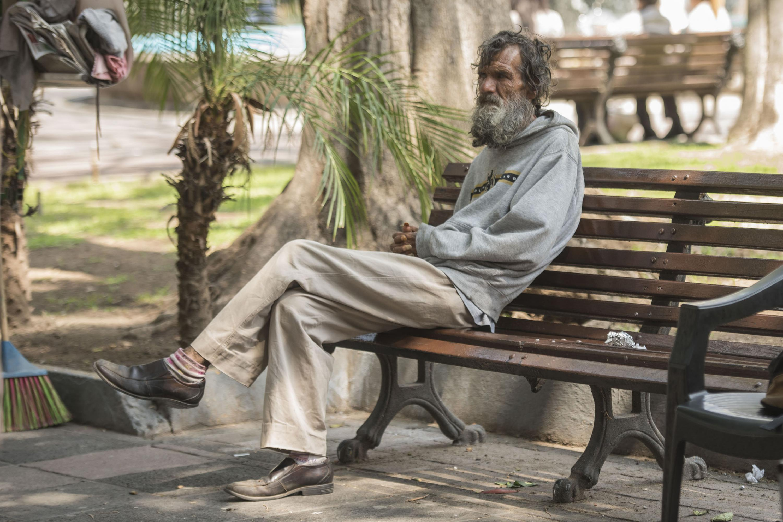 Adulto mayor en estado de indigente, sentado sobre la banca de una plaza del centro de la ciudad.
