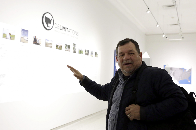 El artista de pie apuntando a la entrada de la exposición