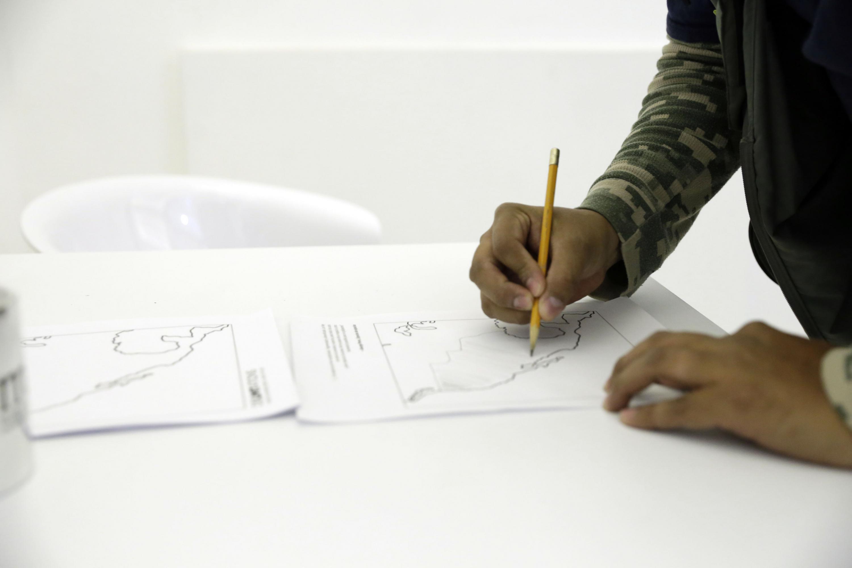El artista dibuja con un lapiz en una mesa completamente blanca