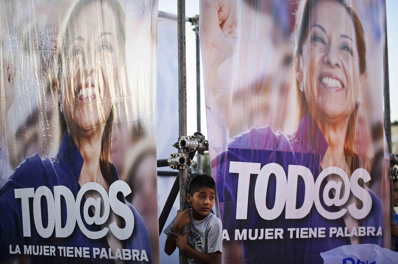 Niño en medio de dos lonas con la imagen de Josefina Vazquez Mota