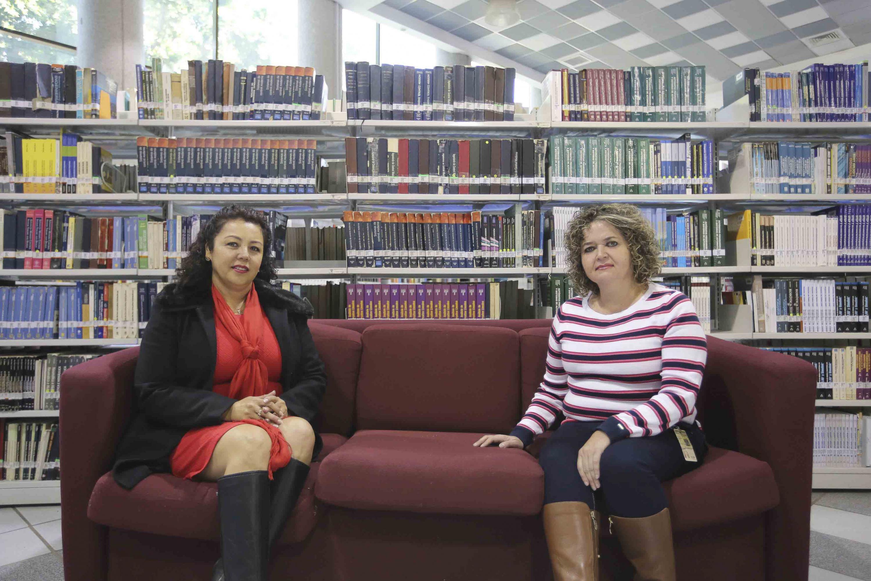 Las doctoras sentadas en un sillon tinto en la biblioteca de CUCEI