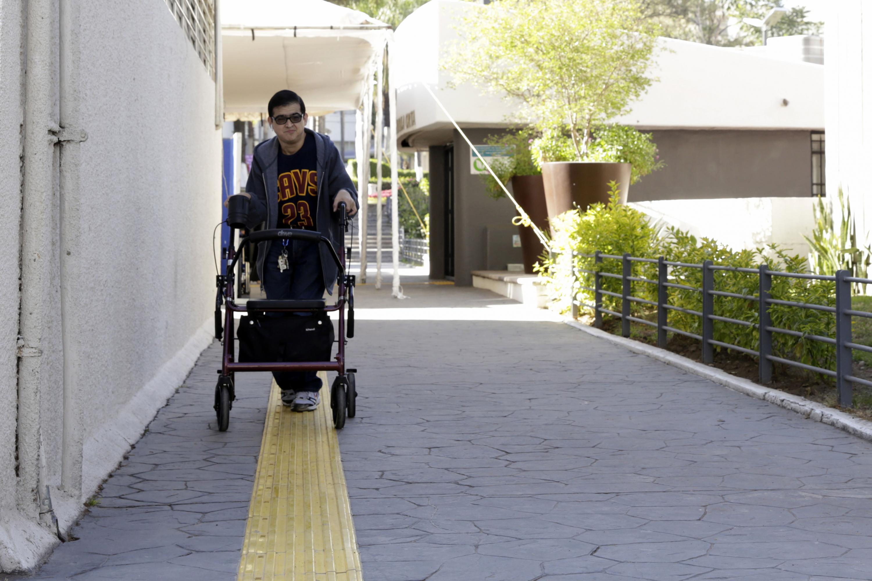 """Joven con discapacidad visual siguiendo la """"Franja-guía de dirección"""", con apoyo de su andadera."""