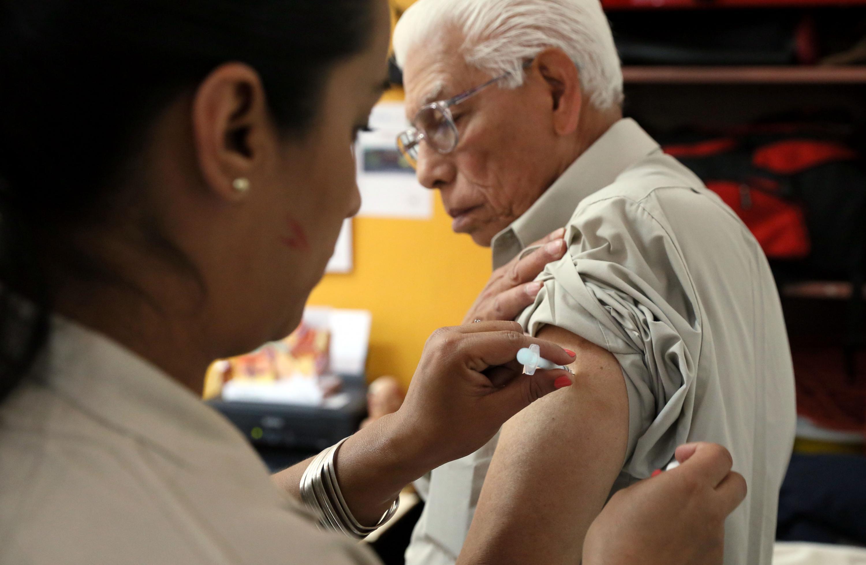 Una enfermera aplica una inyección en el brazo de un adulto mayor