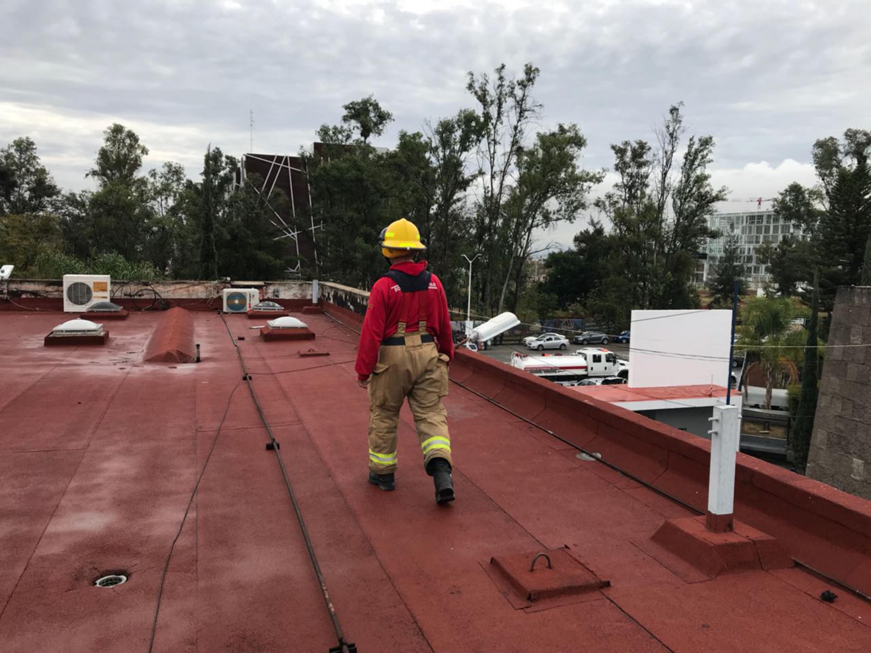 Un hombre de Protección Civil camina por la azotea de un edificio de CUCEA