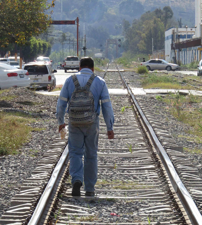 Migrante con mochila en espalda, caminando por las vías ferroviarías de la región.