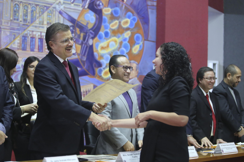 El rector general entregando los diplomas a una de las alumnas de la generación 2018